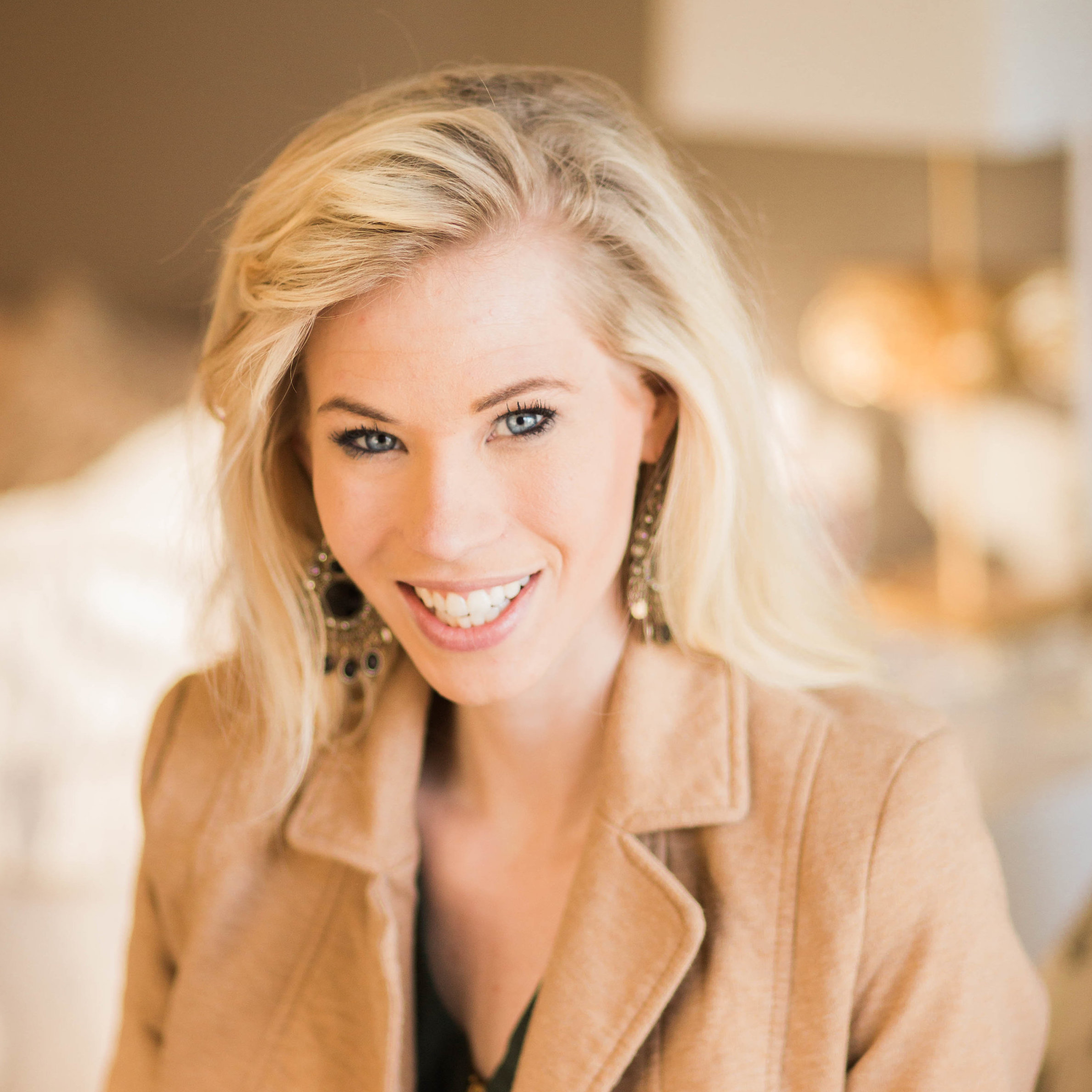 Nicole smiles in front of a blurred background. She has long blonde hair, light-toned skin, and a camel colored jacket.