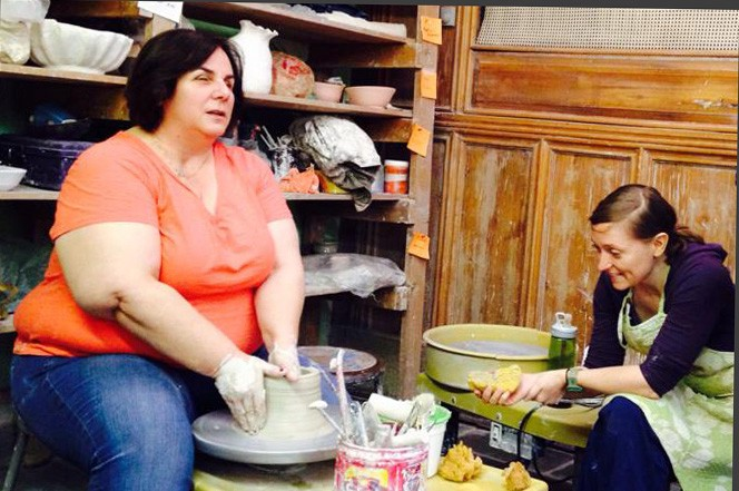 Michelle works with clay on a pottery wheel.