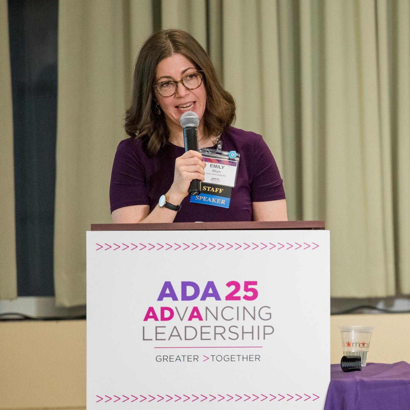 Emily speaks into a mic at a podum with the ADA 25 logo. Brown, medium length hair. Short-sleeved maroon dress, glasses.