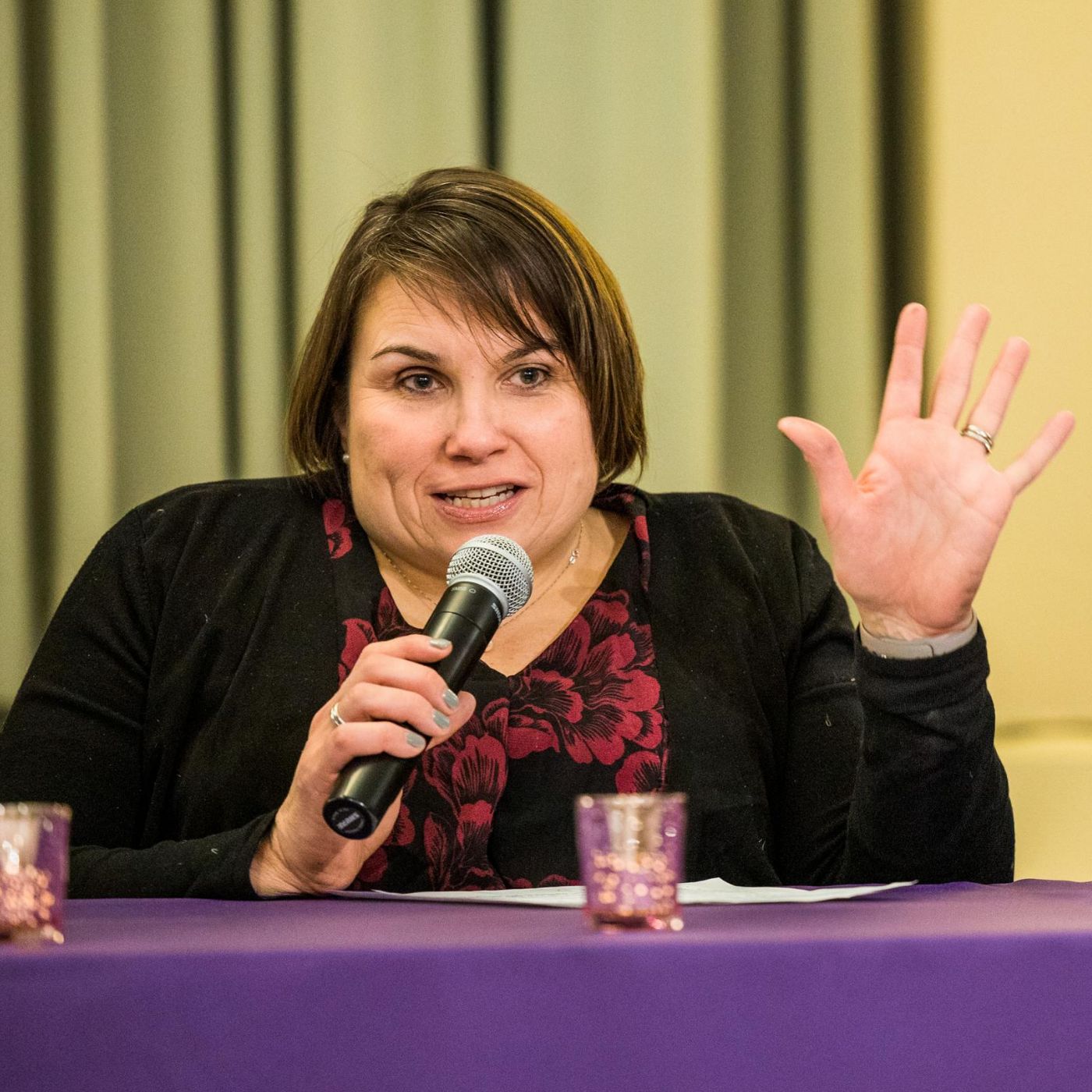 Karen speaks into a microphone, her left hand gesturing outward. Her hair is short, brown. Red floral blouse, black cardigan.