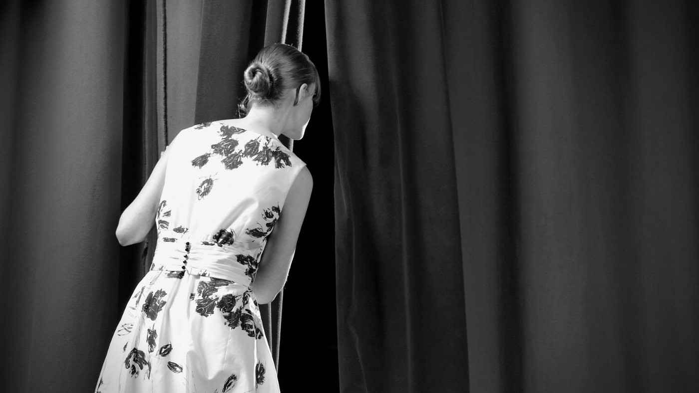 Artsy black and white photo with a rear view of woman in a floral dress peeking through a curtain.