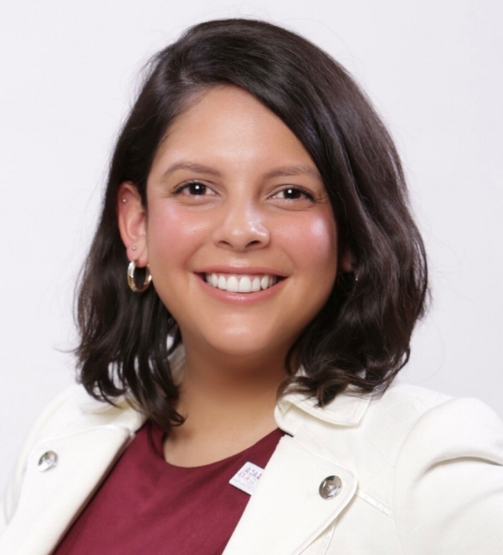 Alex is smiling and posing with her hands on her hips in front of a white backdrop. She is a young Brown Latinx adult woman with short length dark brown hair and is wearing small hoop earrings and a white blazer over a maroon dress.