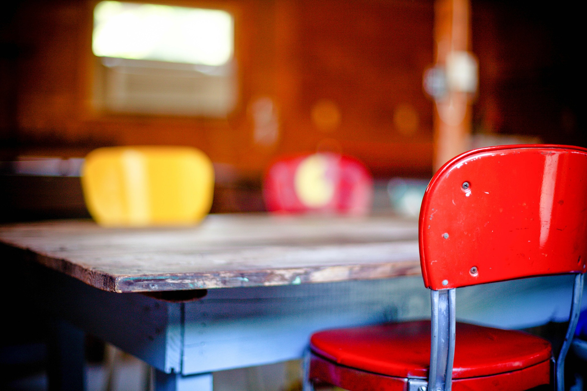 A rustic wooden table with two red chairs and one yellow chair.