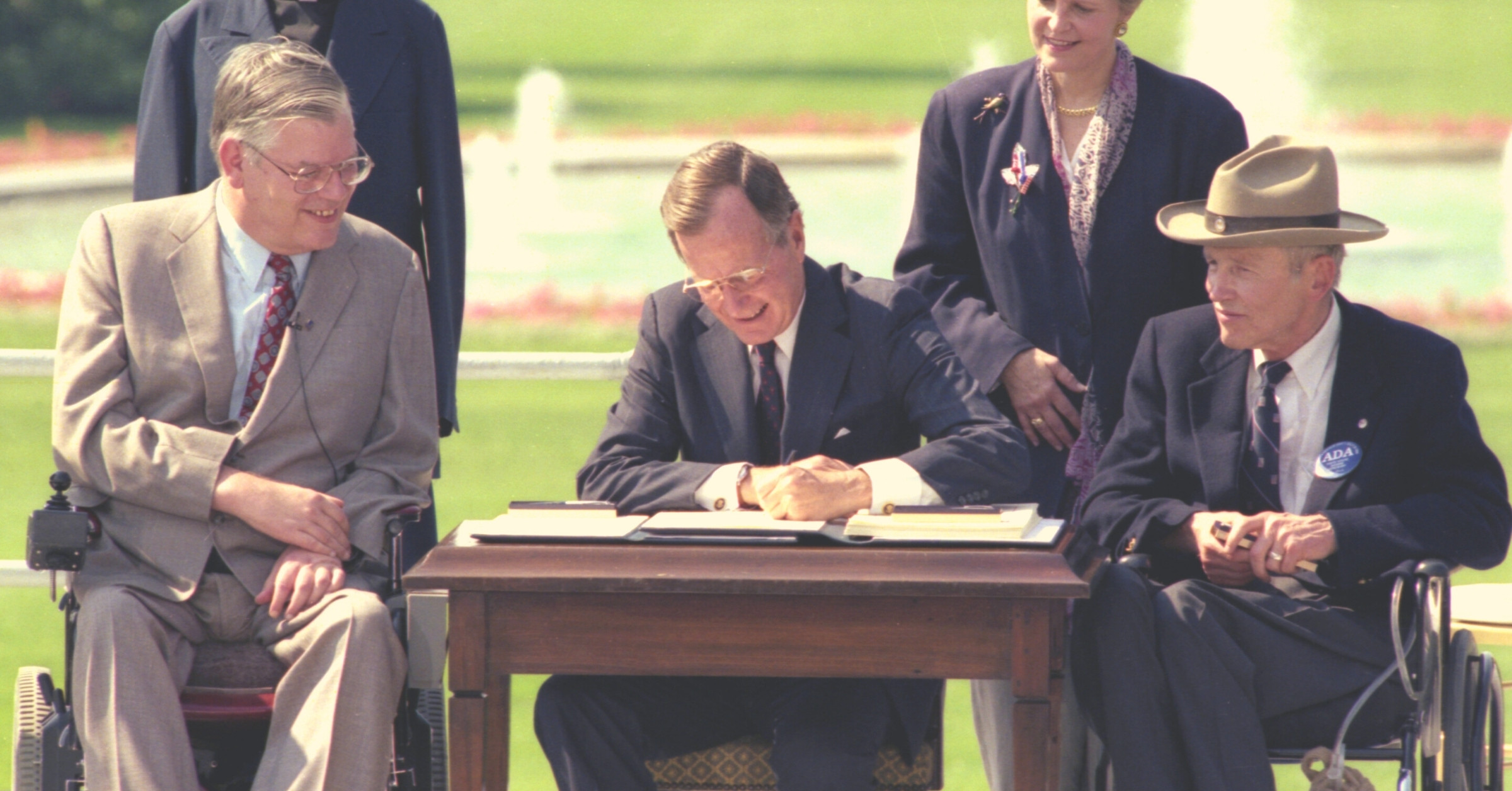 President George Bush signs the ADA in a grassy outdoor setting, as several people watch.