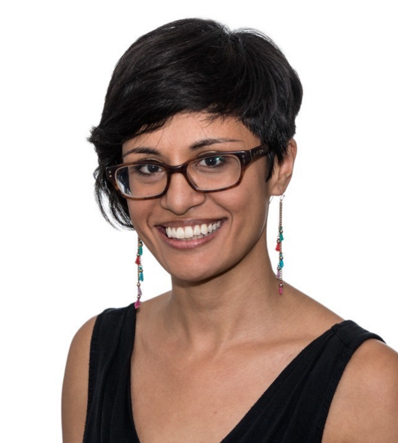 Natasha is a smiling in front of a plain white background. She is a brown Asian woman with black hair and brown eyes. She is wearing brown rectangular glasses, a black top, and colorful, dangling earrings.