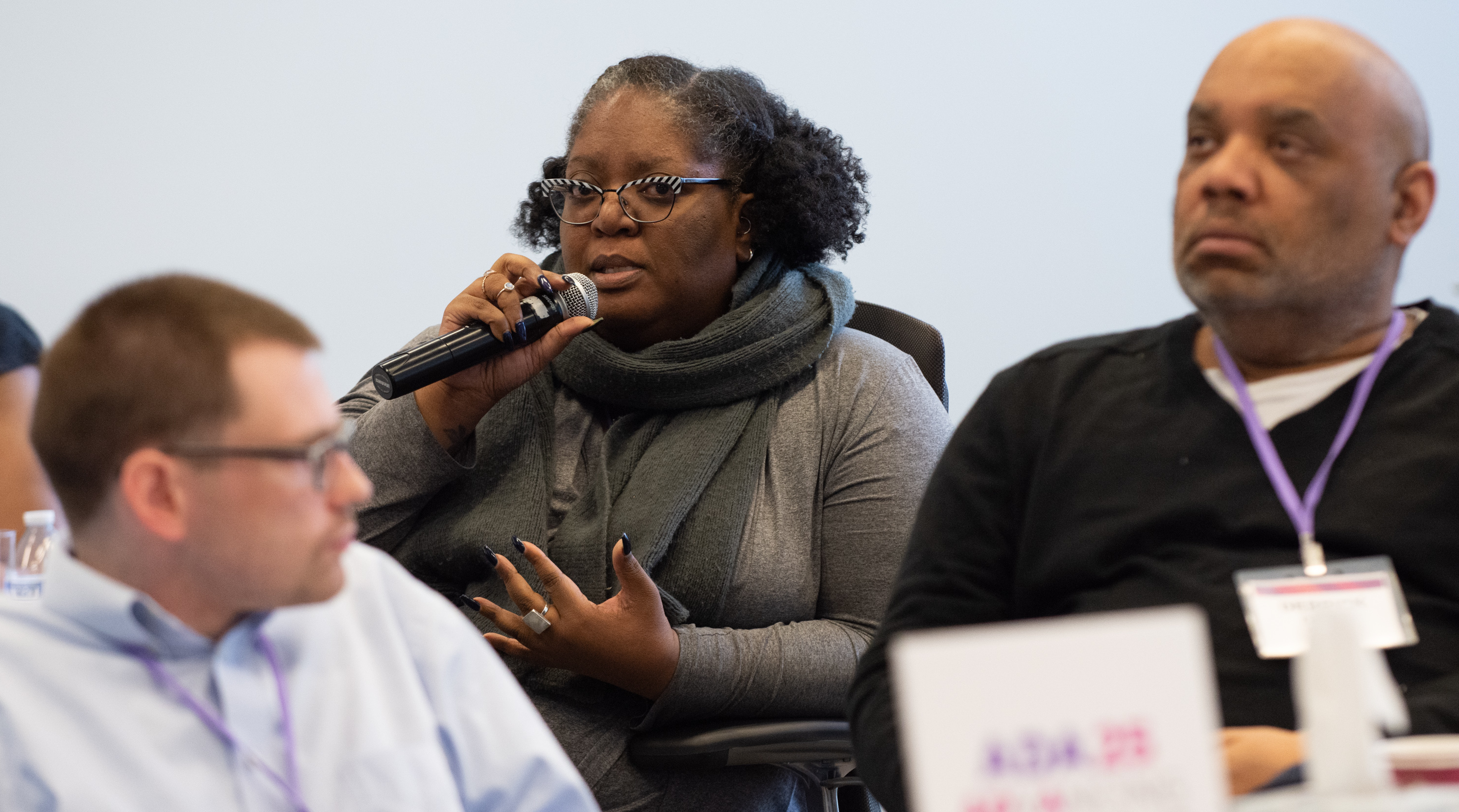 Laura is seated in a room with two other people listening in the foreground. She is speaking into a microphone and her expression is contemplative. She has curly black hair, black and white striped cat-eye glasses, and dark-tone skin.