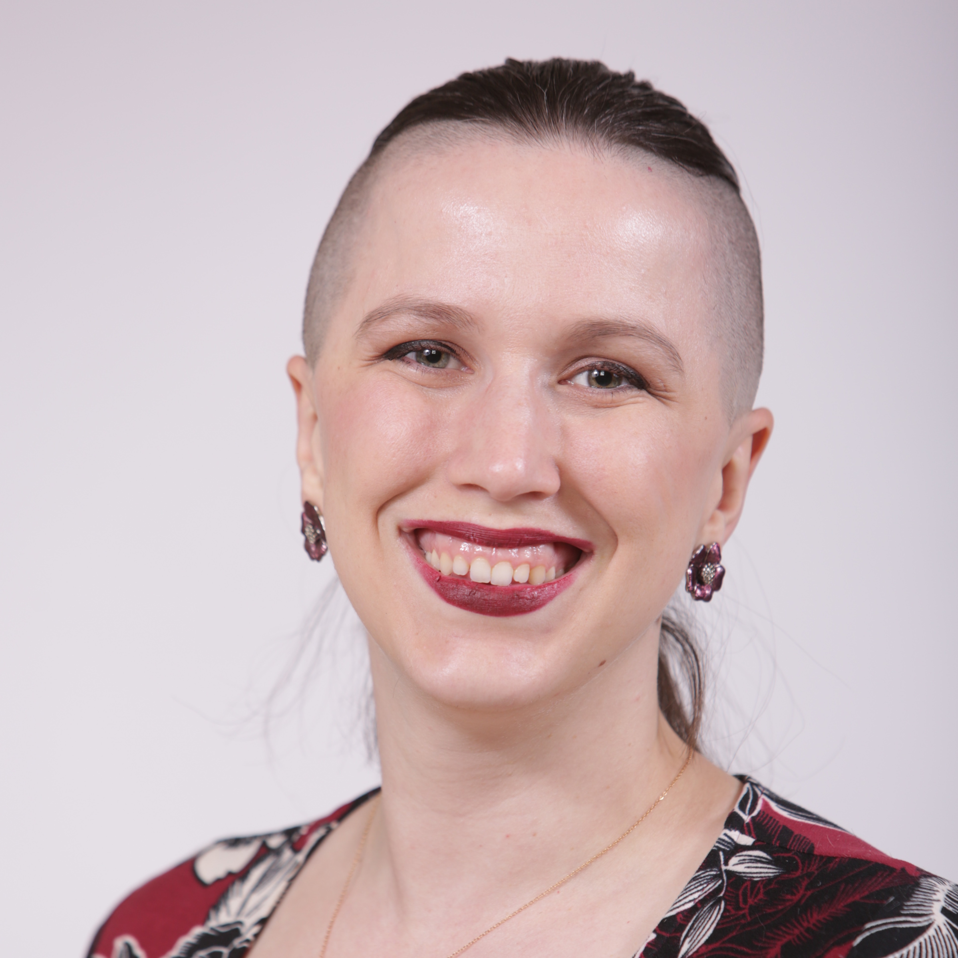 Christea  is smiling against a gray background. The sides of their head are shaved and their brown hair is pulled back into a ponytail, they have light-toned skin, maroon lipstick, silver flower earrings , and a red, white, and black top.