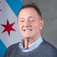 Joe is smiling in front of the Chicago flag.