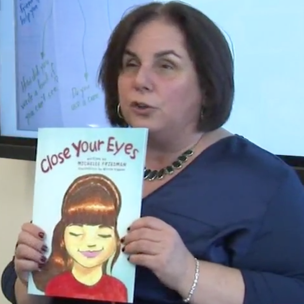 Michelle is reading a book in front of a whiteboard.
