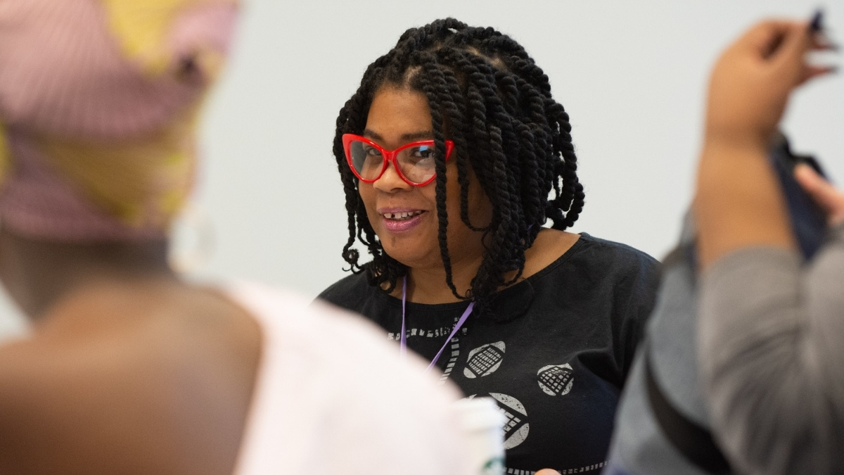 A Black woman peers out from her red cat-eye glasses, smiling at an out-of-focus group of people. Her dark brown hair is in shoulder-length twists.