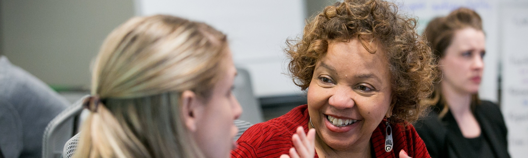 A smiling woman with medium length curly brown hair, medium-dark toned skin, and a red sweater engages in a pleasant conversation.