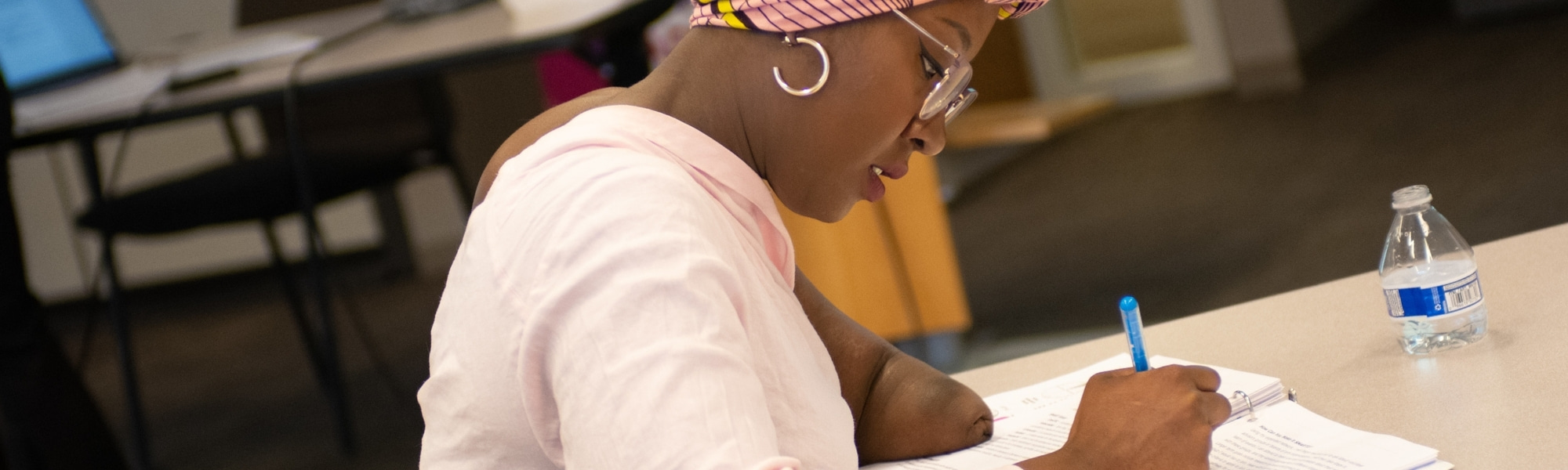 A woman wears a thoughtful expression while writing in a notebook. She has a pink yellow and pink turban, dark-toned skin, silver hoop earrings and is an upper limb amputee.