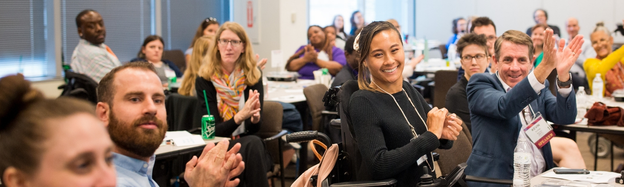 A large room of people sitting at various tables. They are of multiple identities and are cheering, clapping, and smiling. The focus rests on a smiling woman with pulled back black hair, medium-toned skin, and is using a power chair.