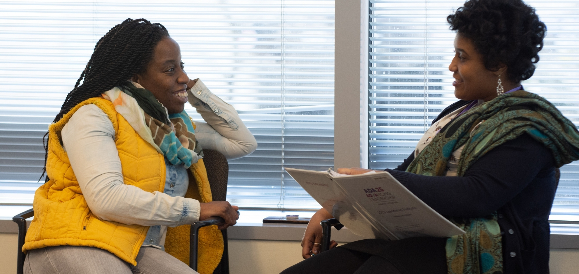 Two women sit by a window smiling at each other. One has long black braids, dark-toned skin, and a yellow puffy vest. The other has curly dark brown hair, dark-toned skin, and dangly diamond earrings.