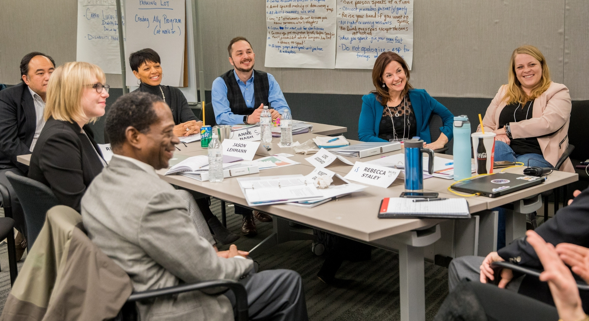 A group of people of various ages, races, genders, and abilities sit around a messy conference table covered in papers and refreshments, smiling at someone off camera.