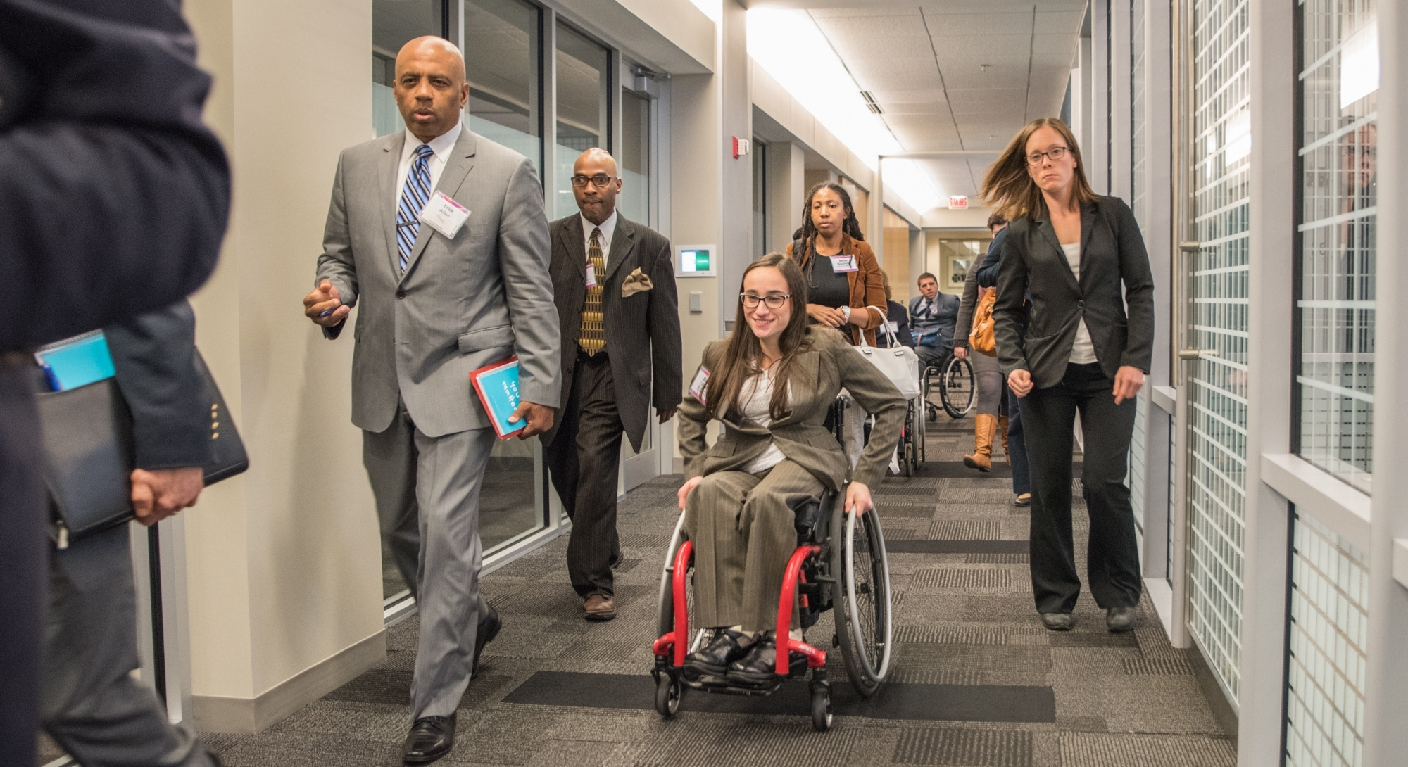 A group of individuals with various identities and abilities navigate a long hallway.