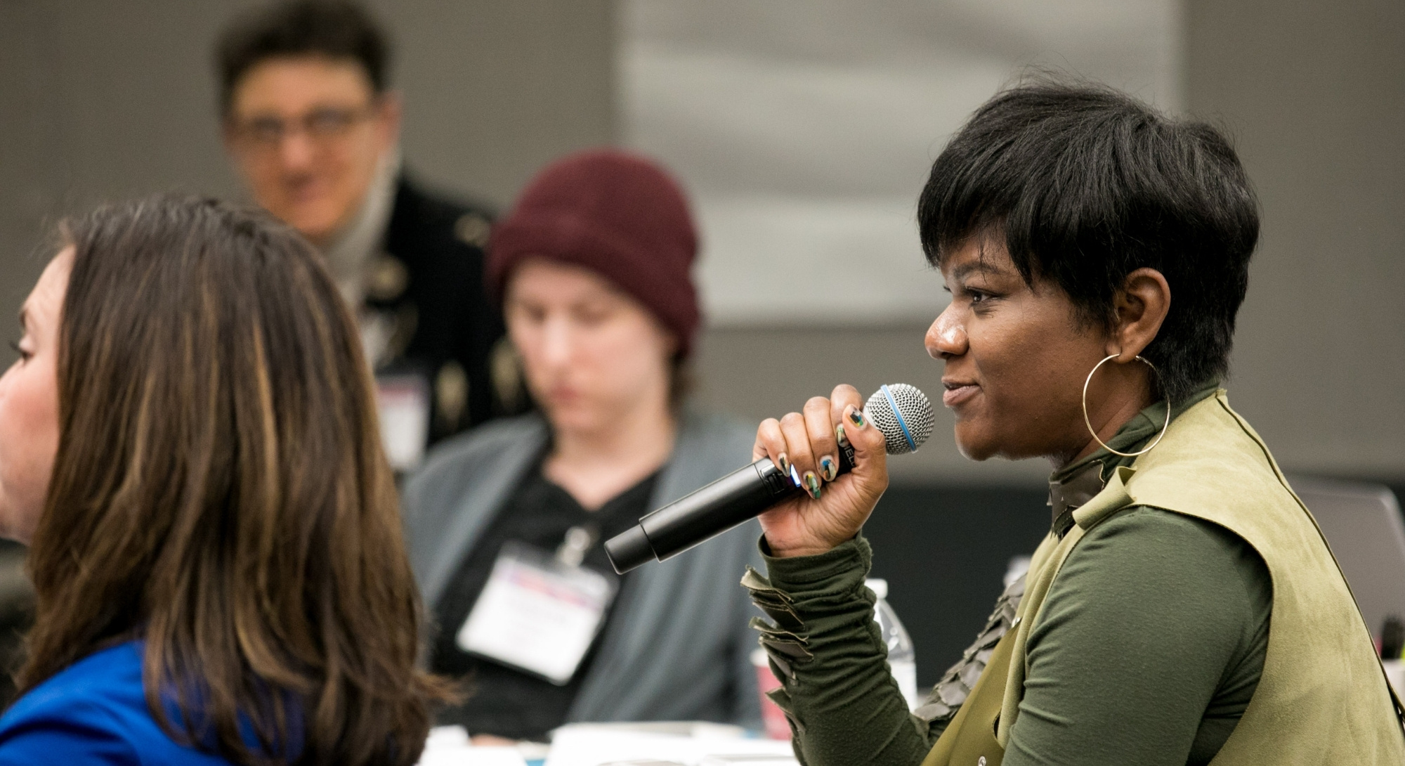 A woman with short black hair, dark-toned skin, and a green top addresses a conference room of people with a microphone.