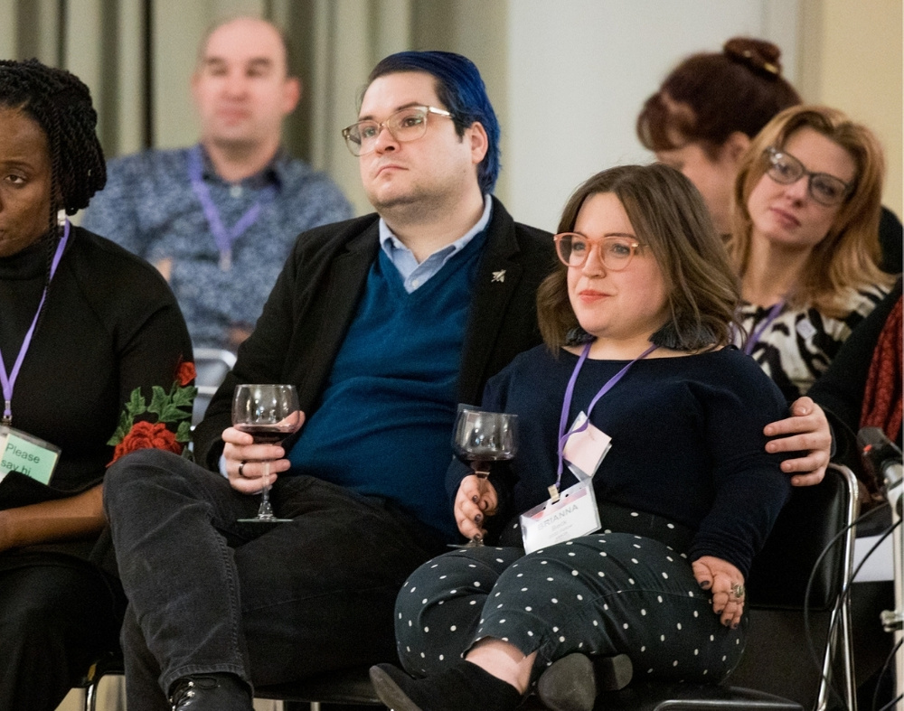 A crowd of various identities listens attentively. Some are holding wine glasses.