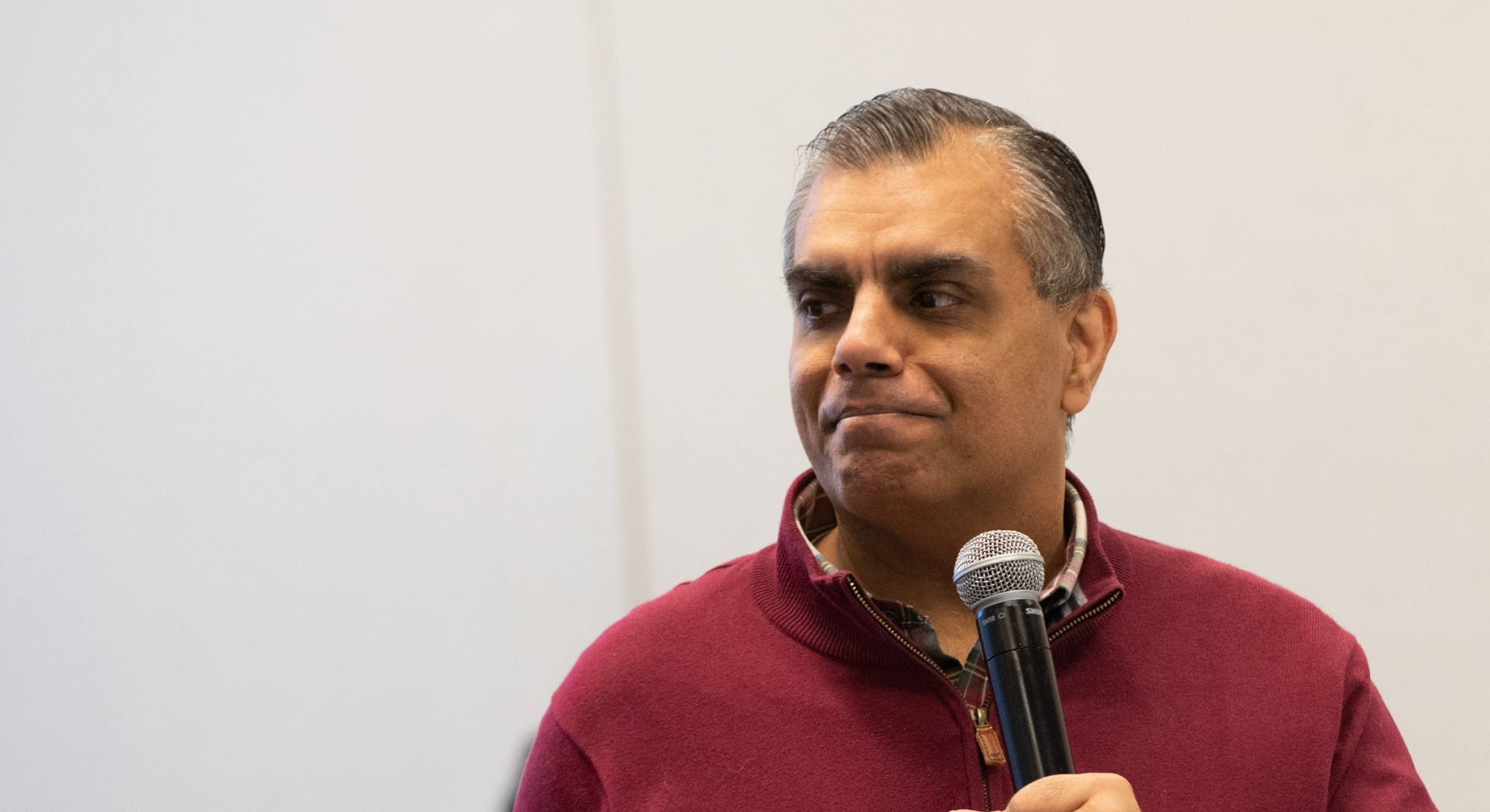 A man with short thinning gray hair, medium-dark toned skin, and a red sweater smiles emotionally while holding a microphone.