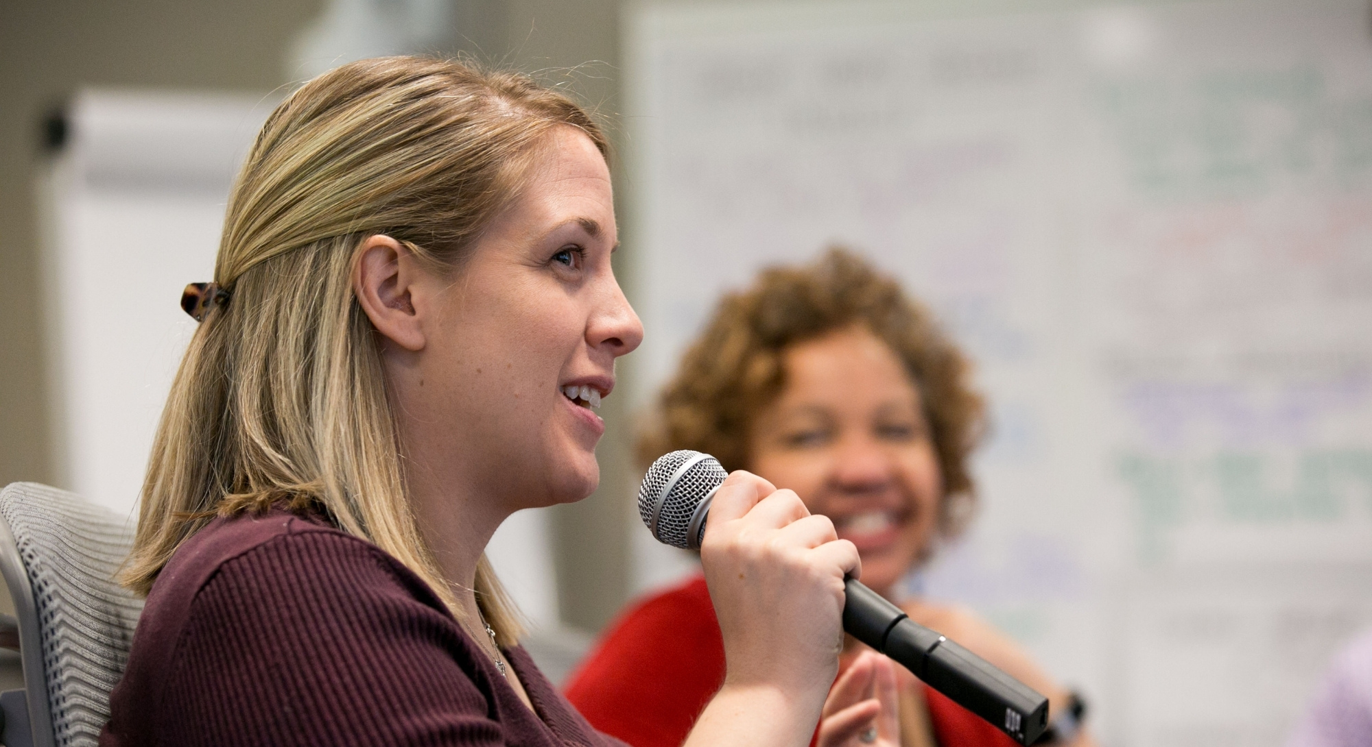 A woman with blonde hair, medium-light toned skin, and a brown cardigan speaks into a microphone in a conference room.