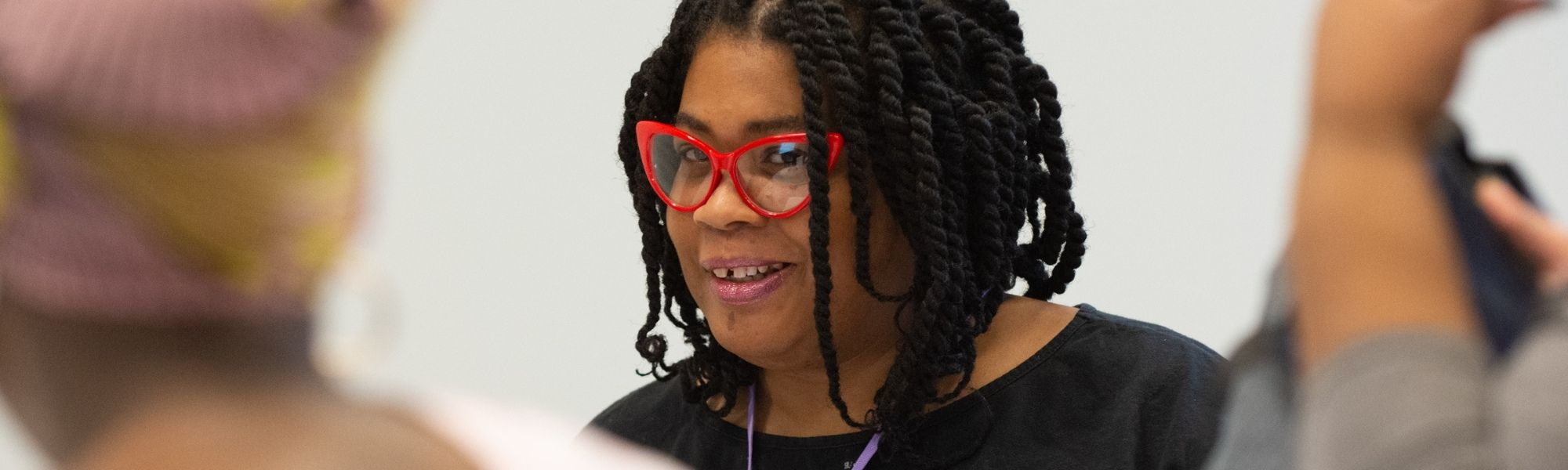 a smiling black woman with shoulder-length twists and a black tee peers through red cat-eye glasses amidst an out-of-focus group of people.