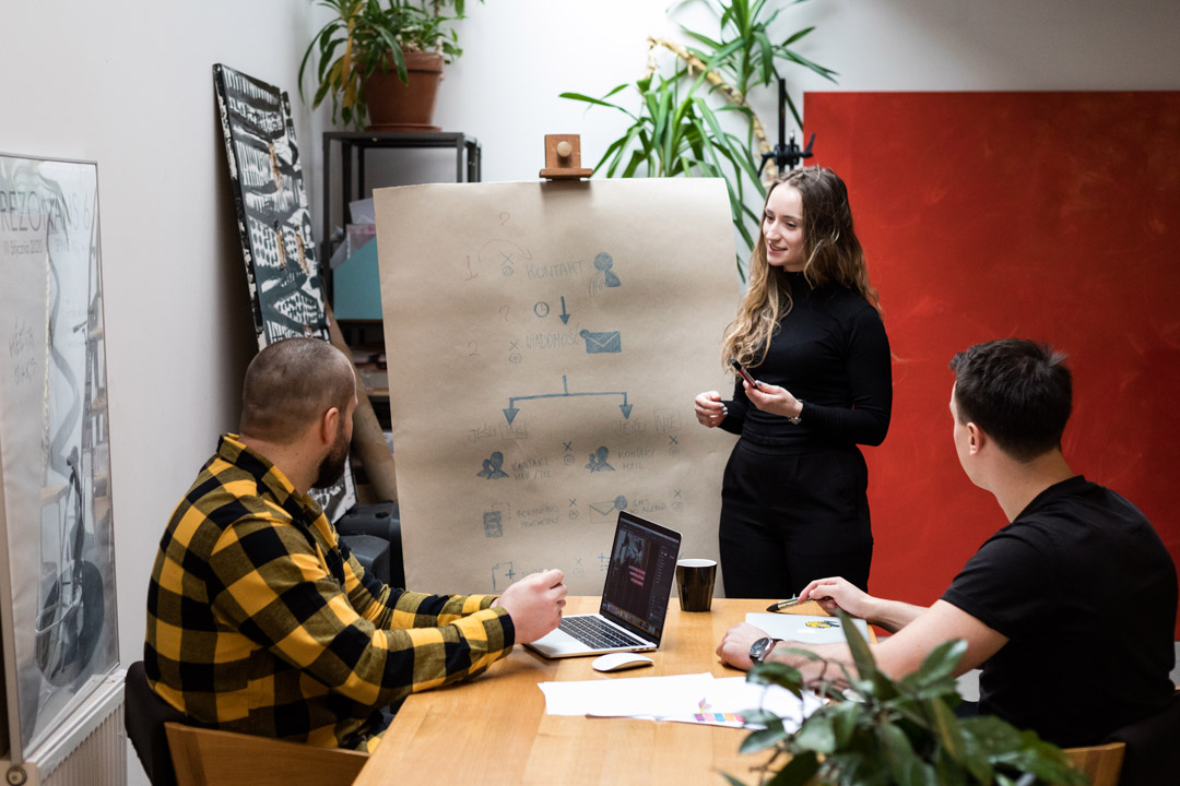 Uśmiechnięta Gosia stojąca przy tablicy podczas prezentacji planu działania