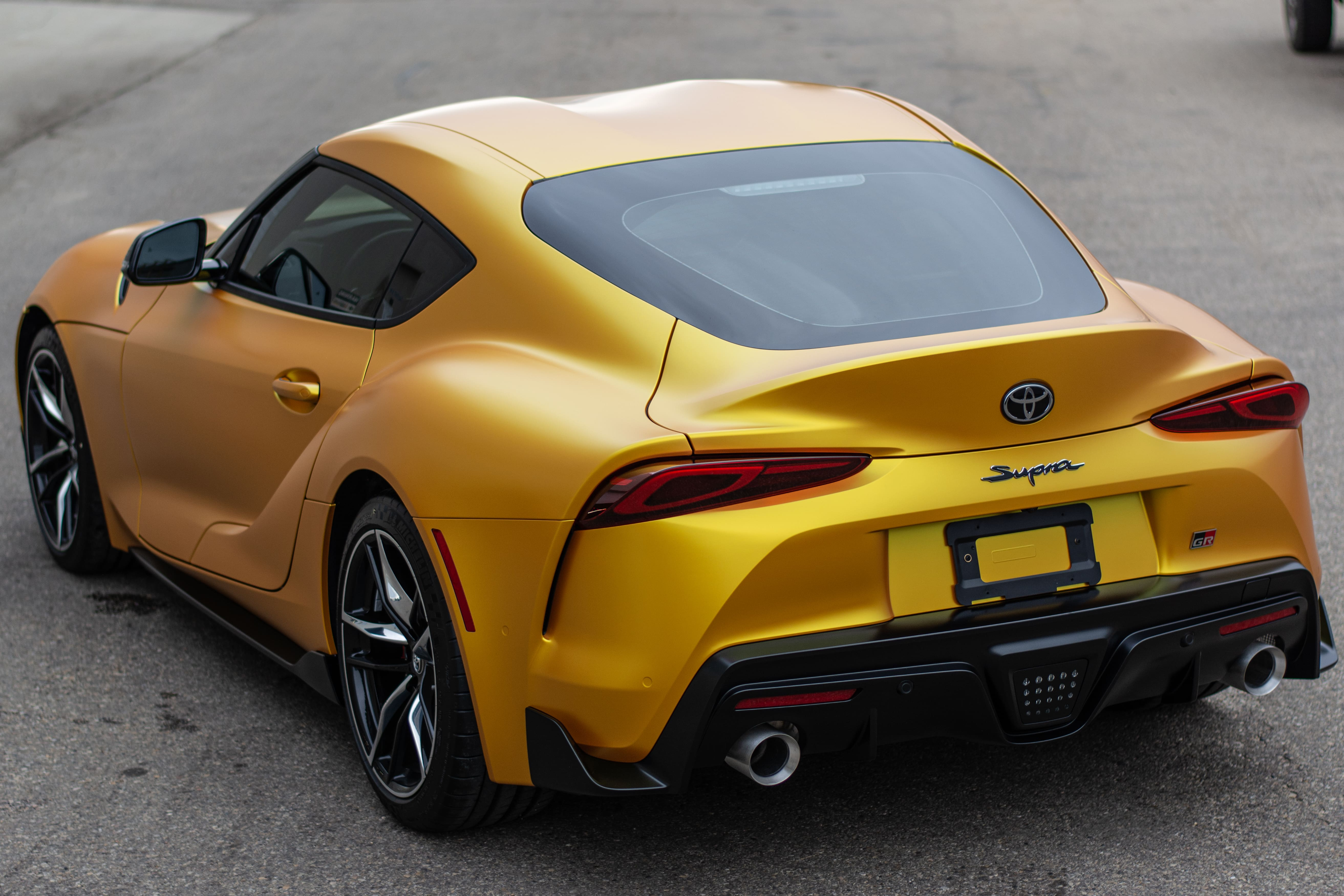 Golden Yellow wrapped Toyota Supra image taken from behind.
