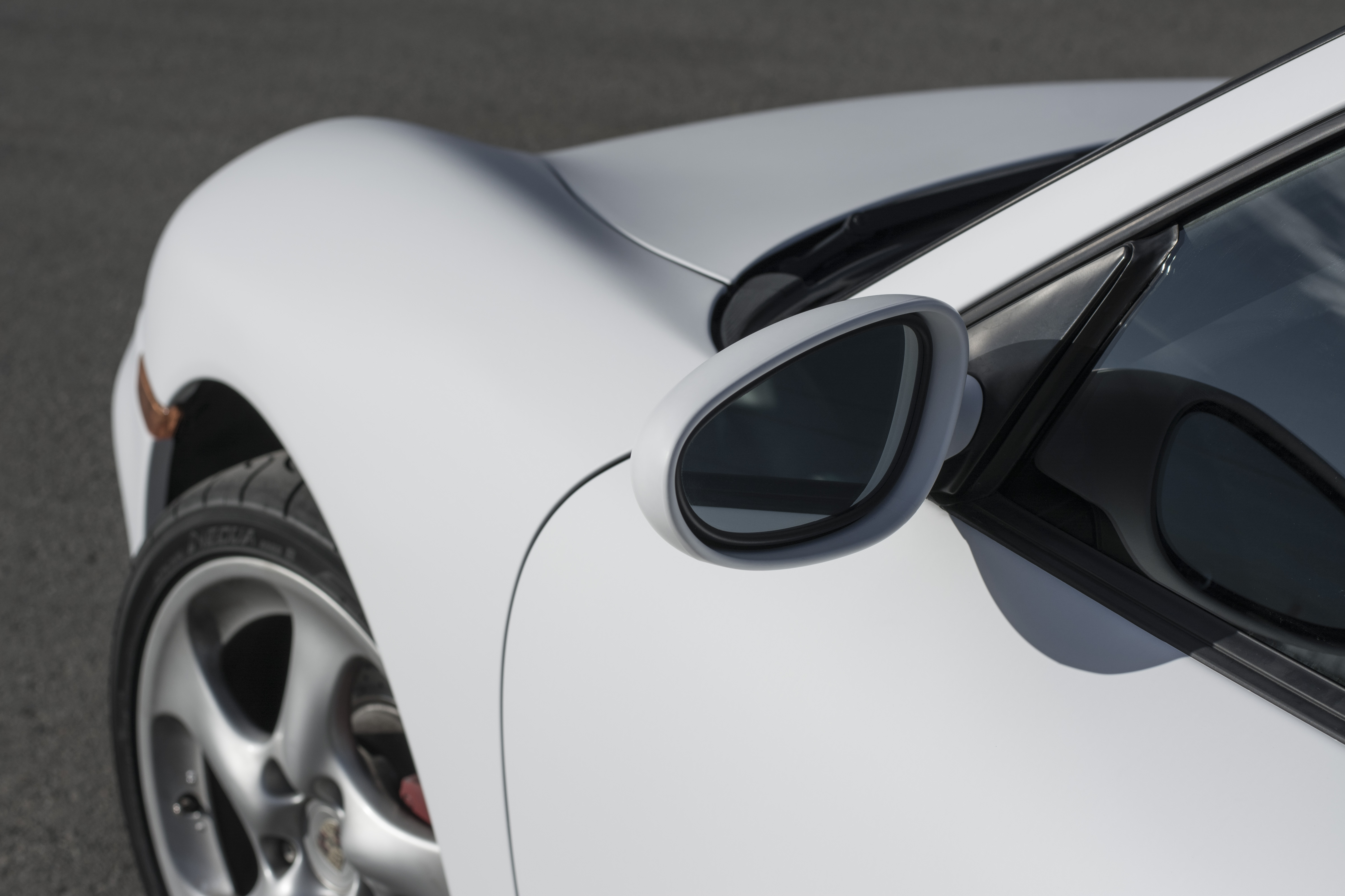 A vinyl wrapped mate white Porsche. Image of the left door and mirror.