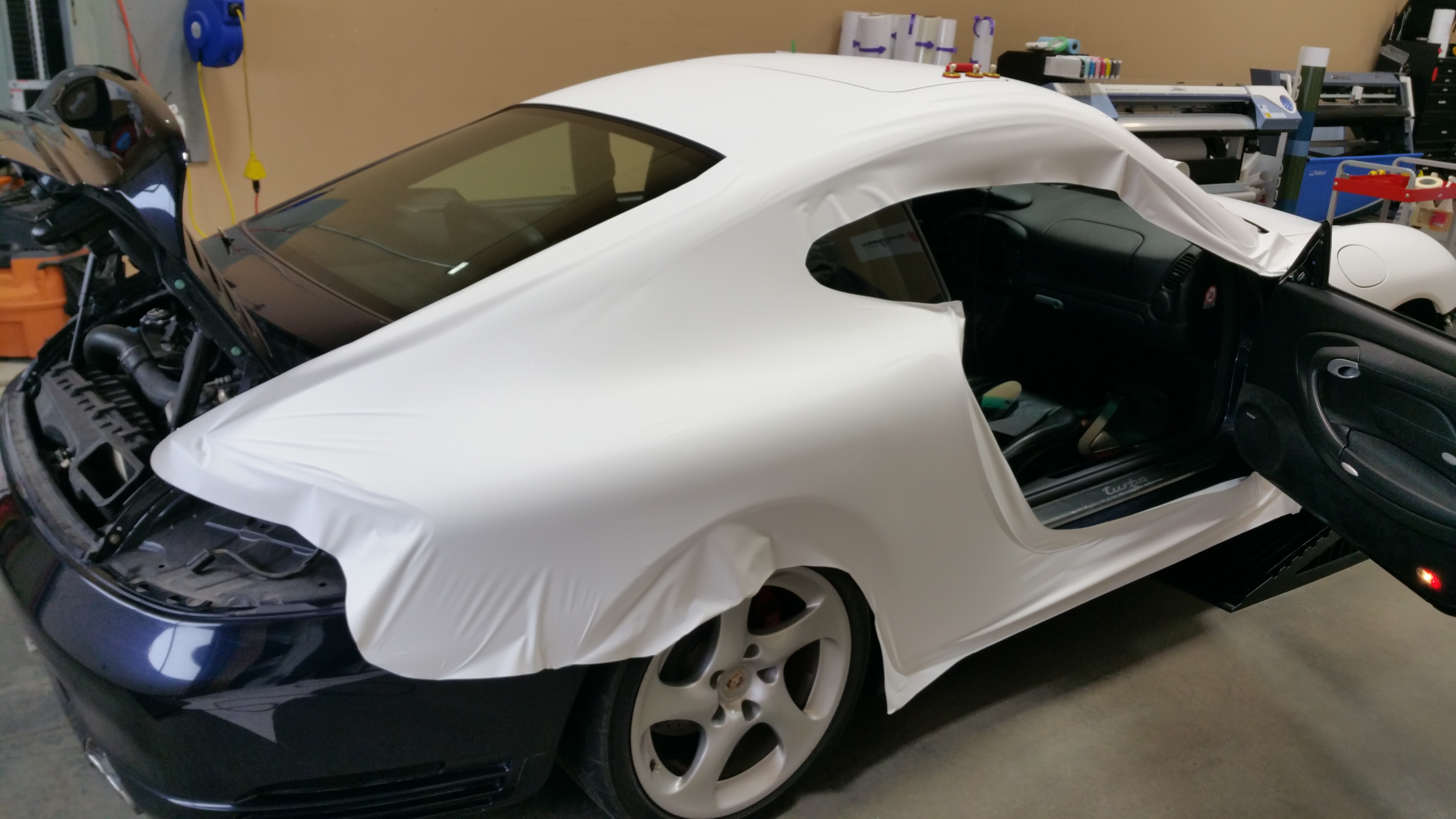 Porsche's right door and side during wrapping process.