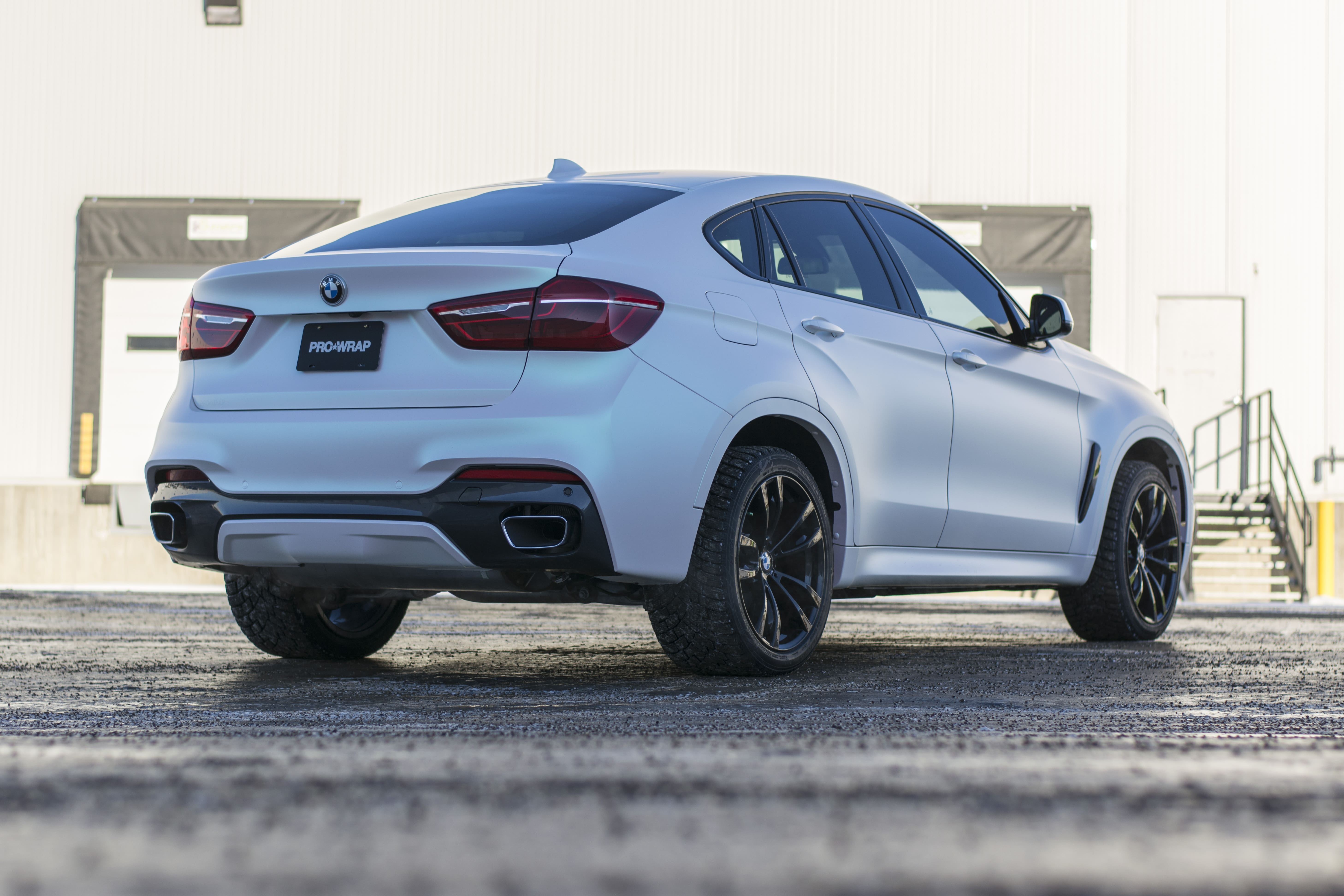 BMW X8 wrapped in KPMF Matte Aurora Pearl from behind left.