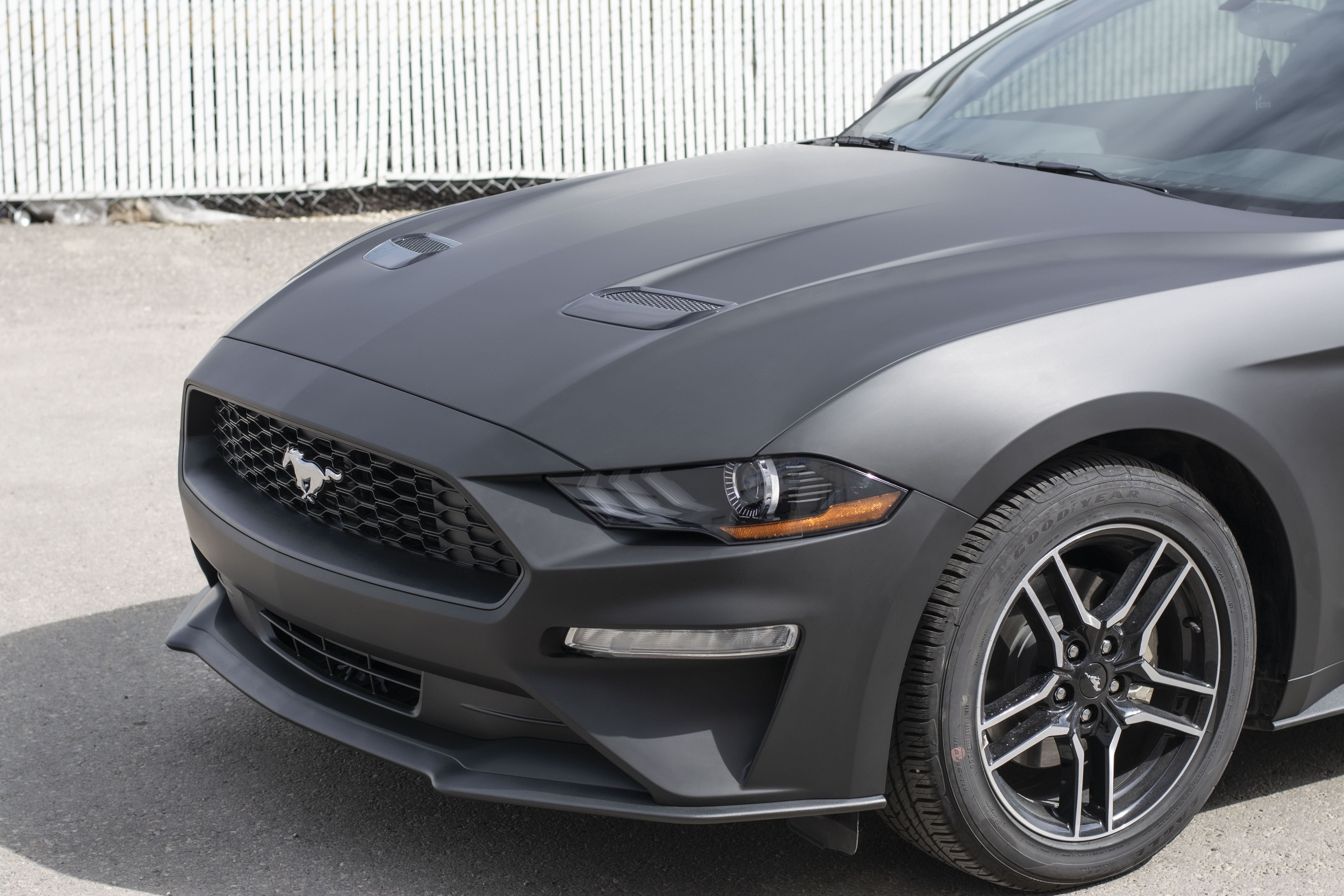 Ford Mustang wrapped in Avery Matte Black from front on the right side.