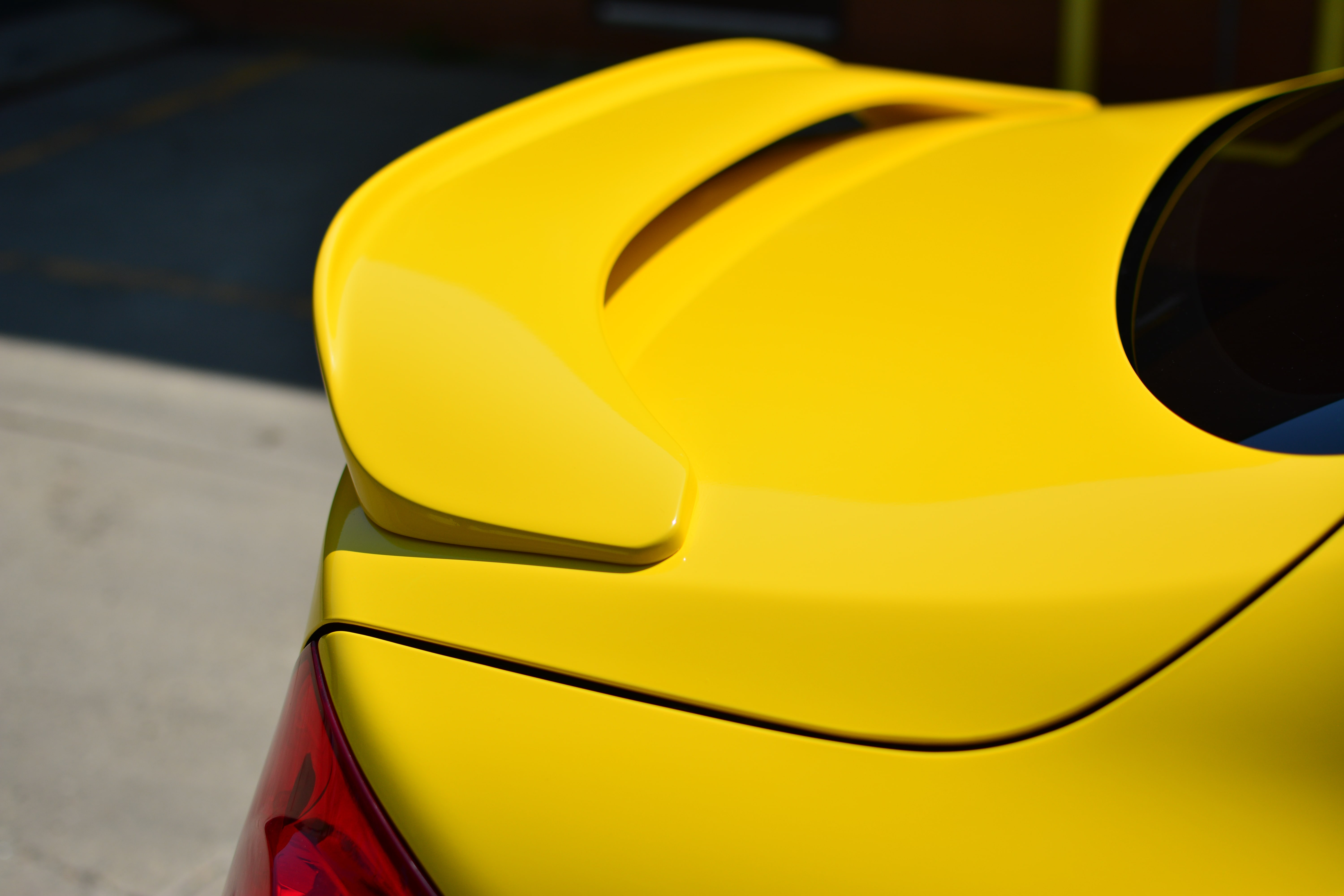 Infiniti G37 wrapped in 3M Gloss Yellow tailgate from side.