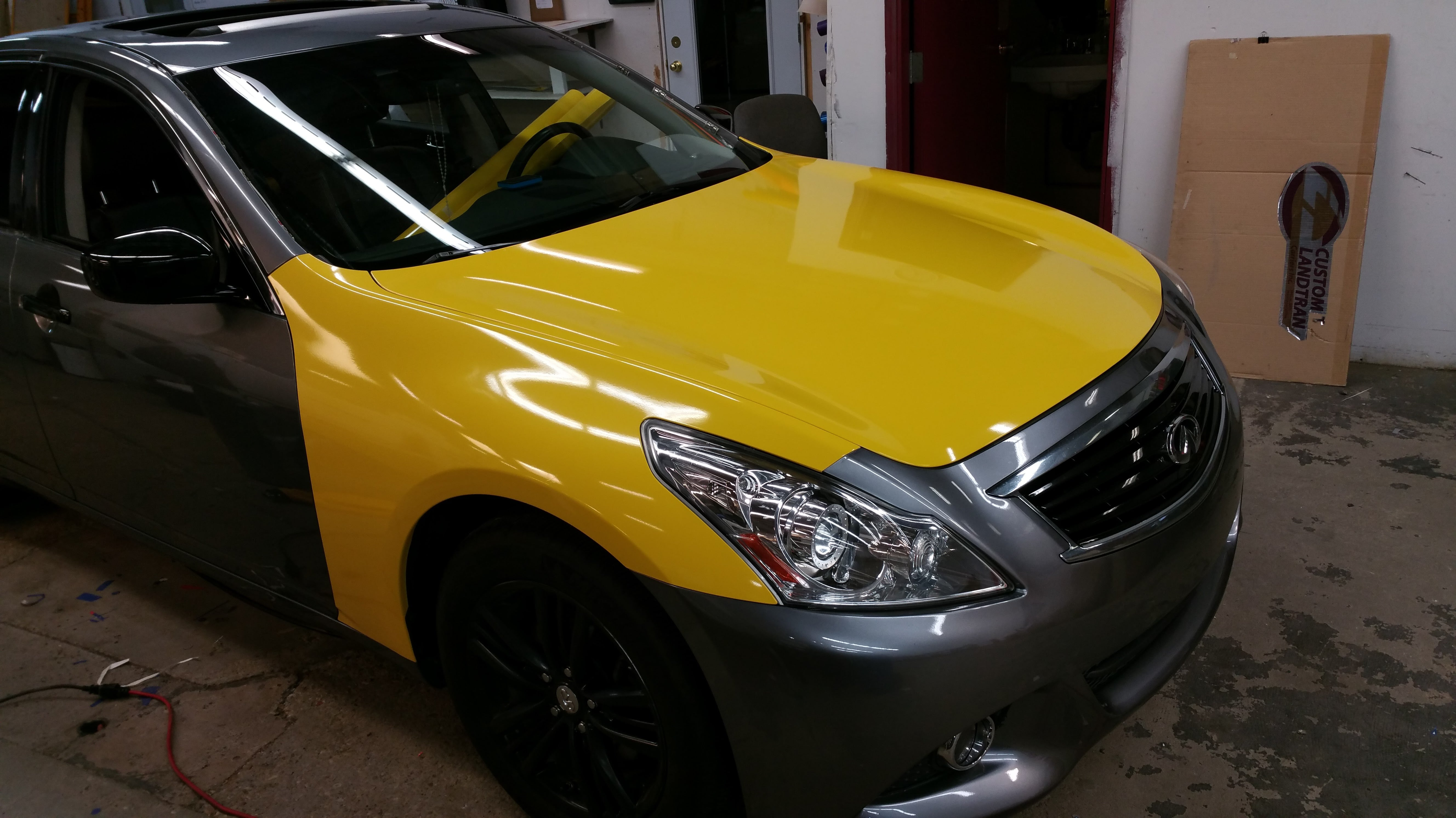 Infiniti G37 during wrapping process, hood wrapped in 3M Gloss Yellow.