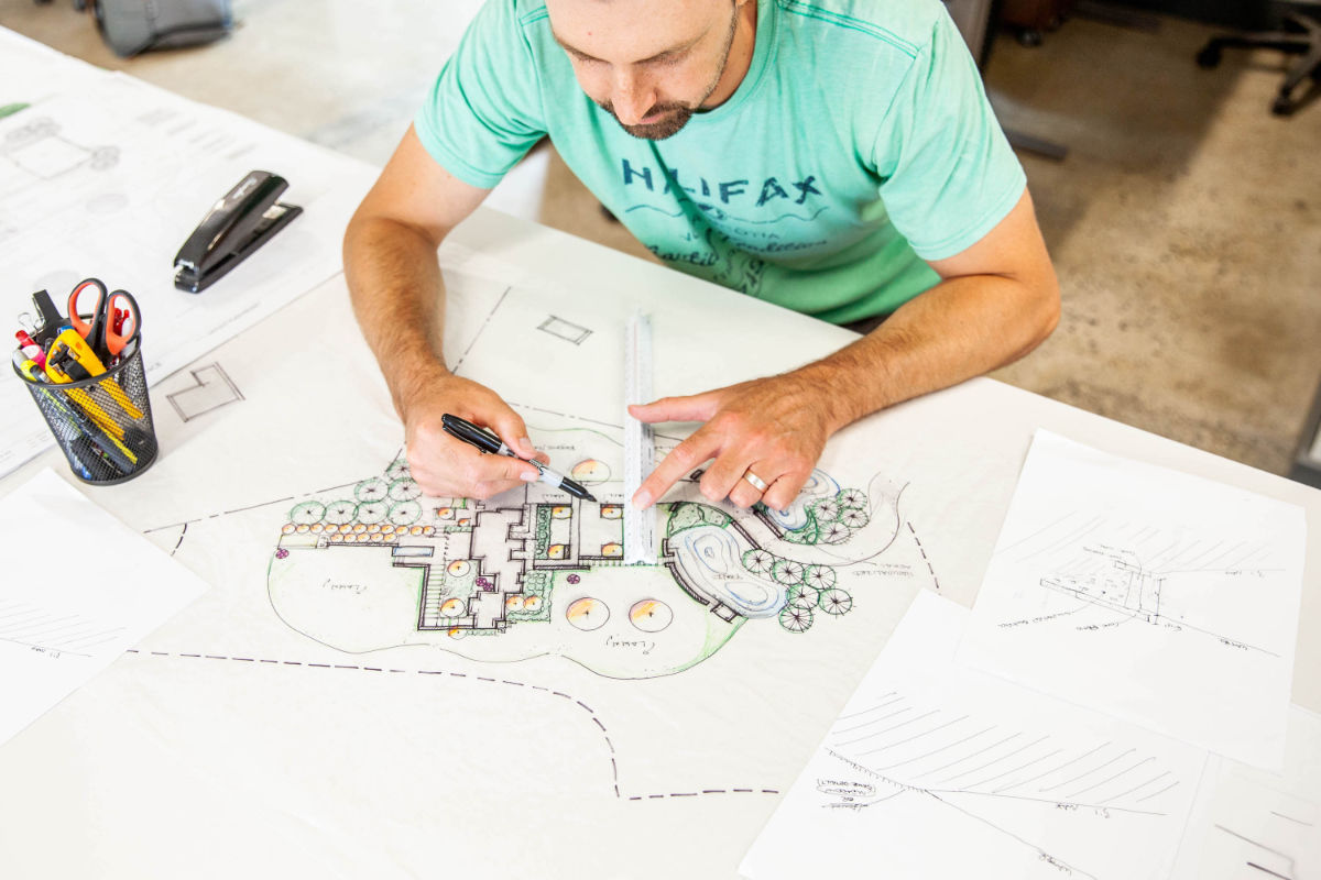 A worker drawing up their landscape design idea while siting in an office.