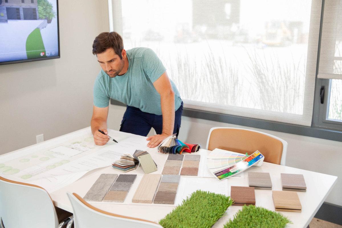 A worker going over a landscape design inside an office.