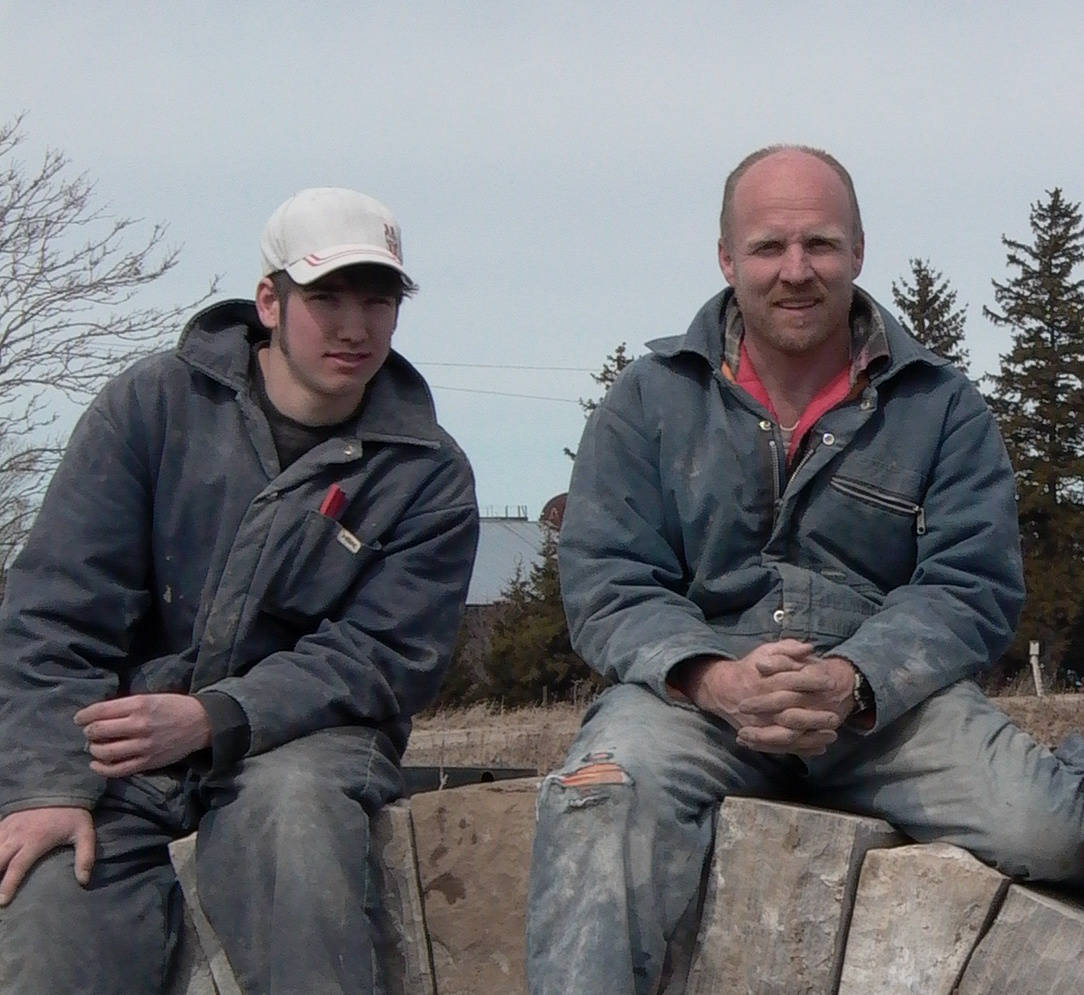 Father and son sitting on a stone fence wearing blue jackets and jeans.