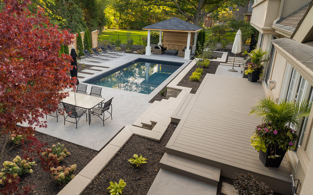 A large backyard with a swimming pool surrounded by large cement tiles and an uncovered patio attached to the house.
