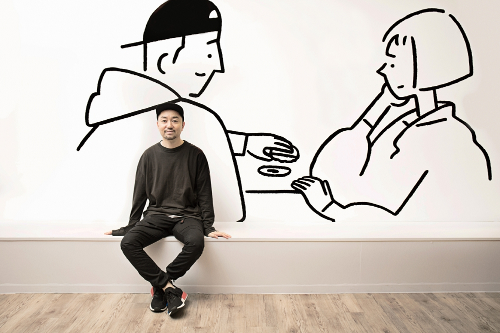 Artist Yu Nagaba sitting in front of one of his murals. - Credit: BANG Magazine (2018)