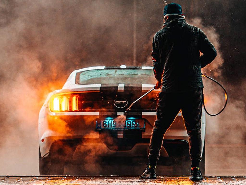 Image of man pressure washing his car