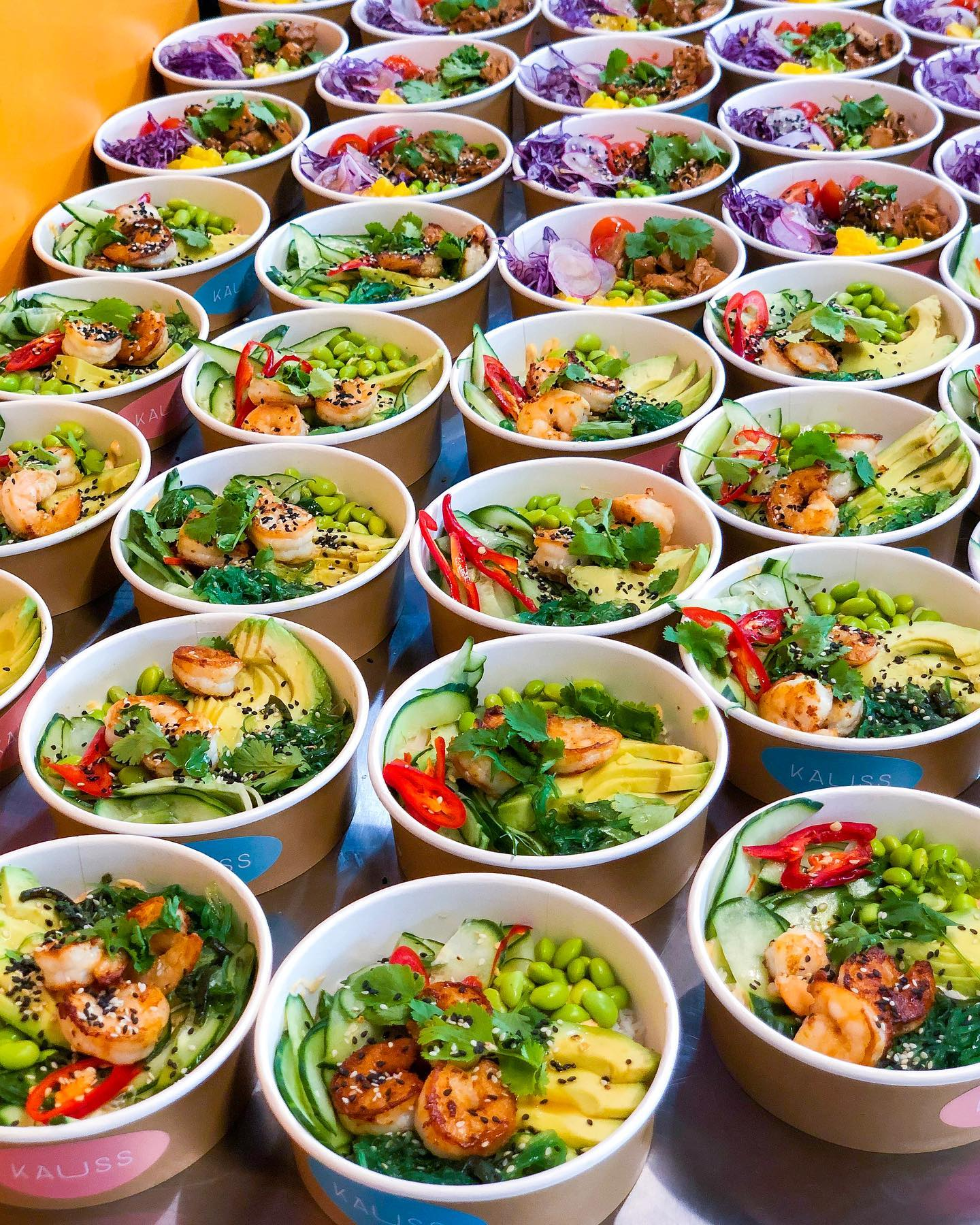 Table full of multiple rows of poke bowls with lush toppings and colorful veggies
