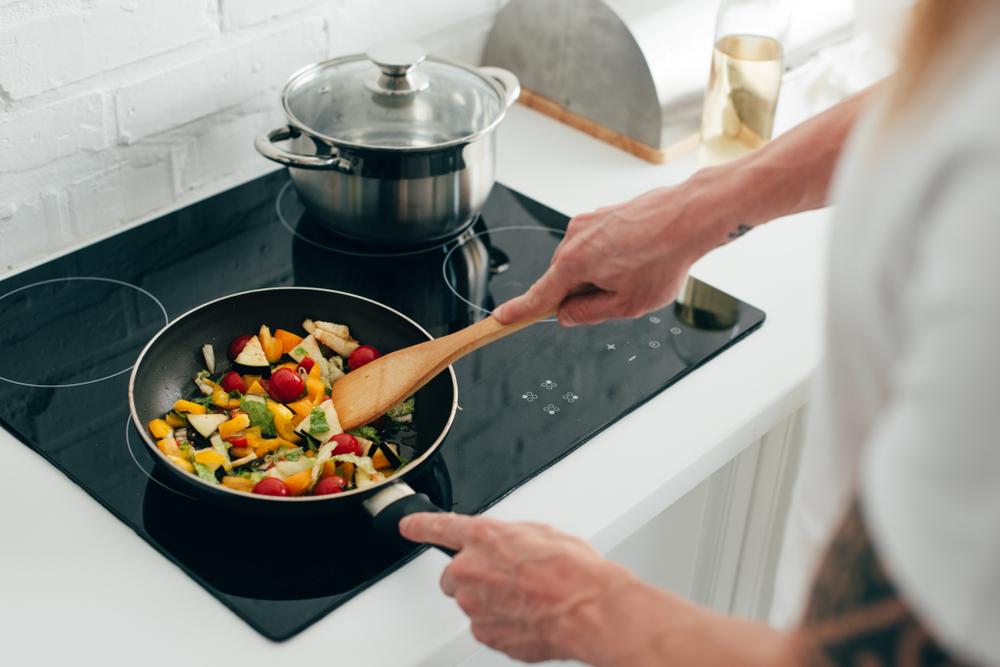 Homme faisant revenir des légumes dans une poêle