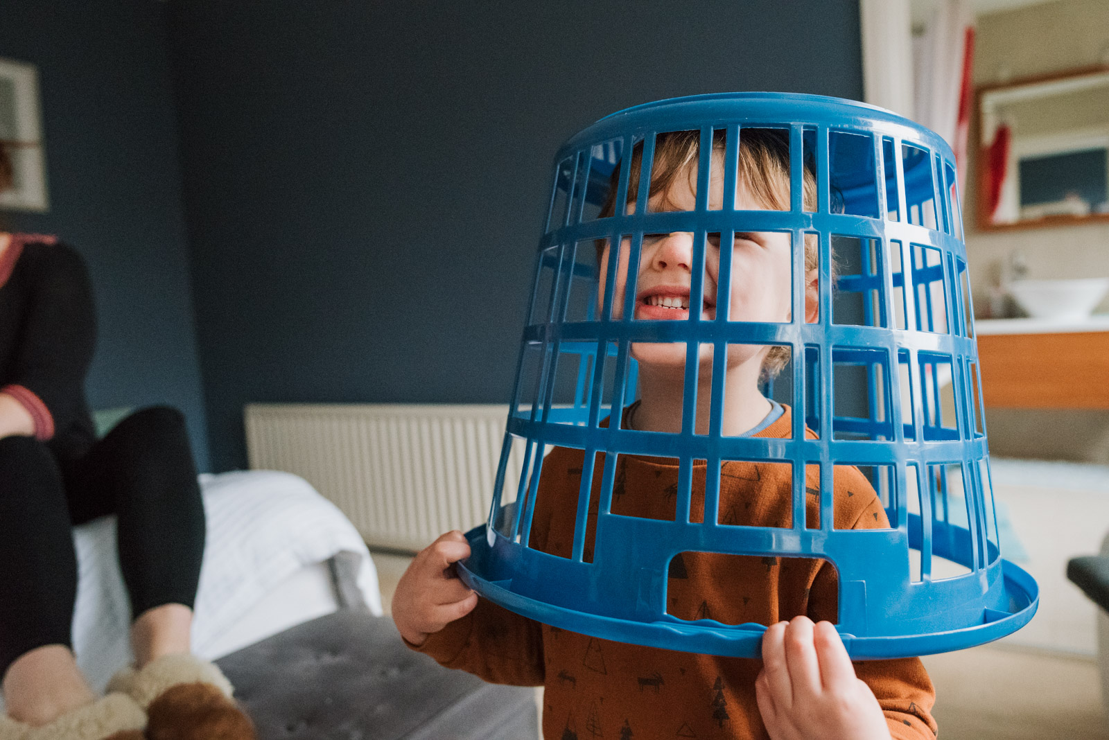 Best Hampshire family photographer, boy laughing in a laundry basket