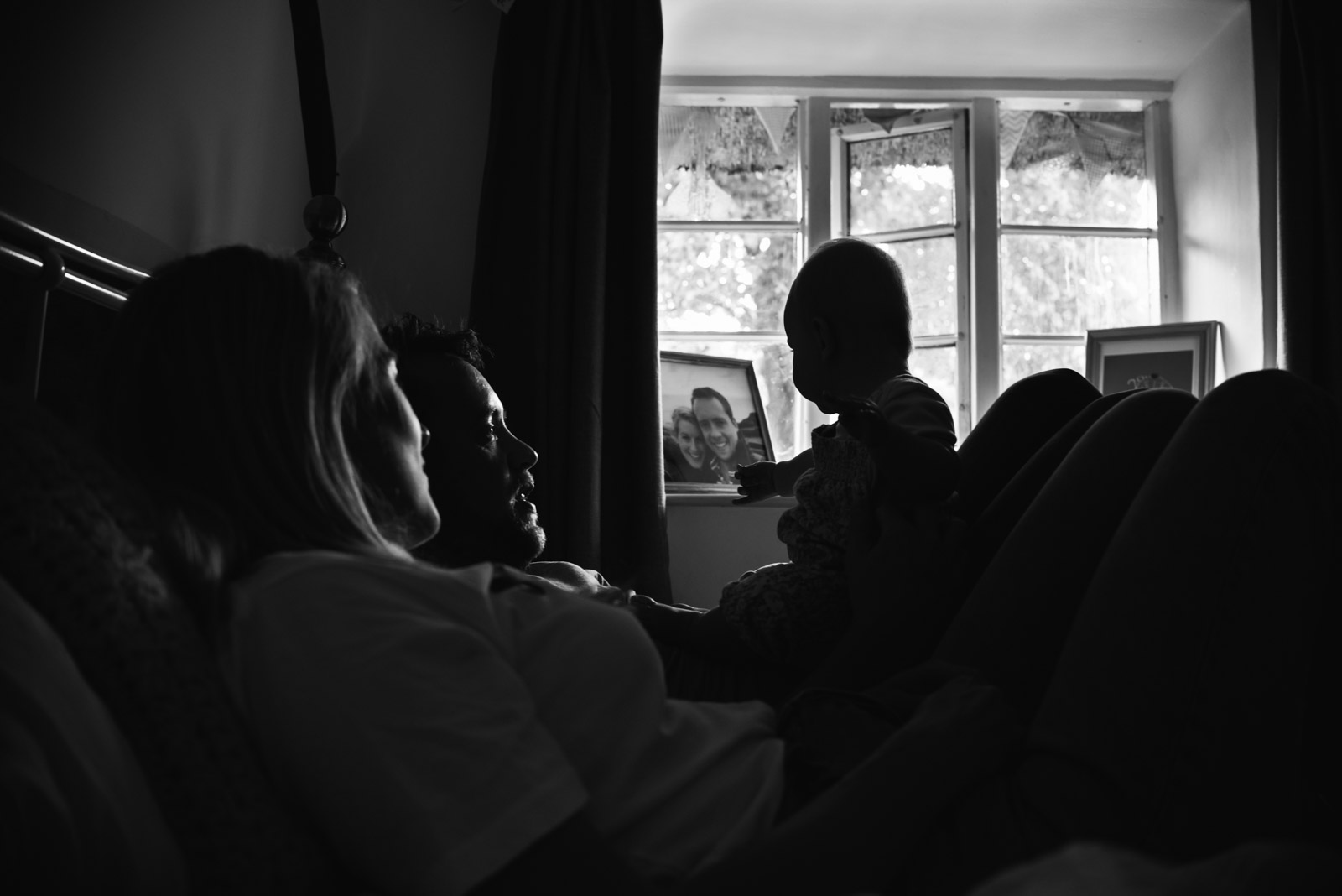Documentary family photography of Mum and Dad playing with baby in Wiltshire