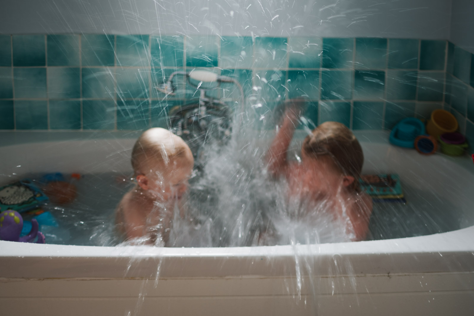 Girls playing in the bath by a Relaxed and natural family photographer in Berkshire