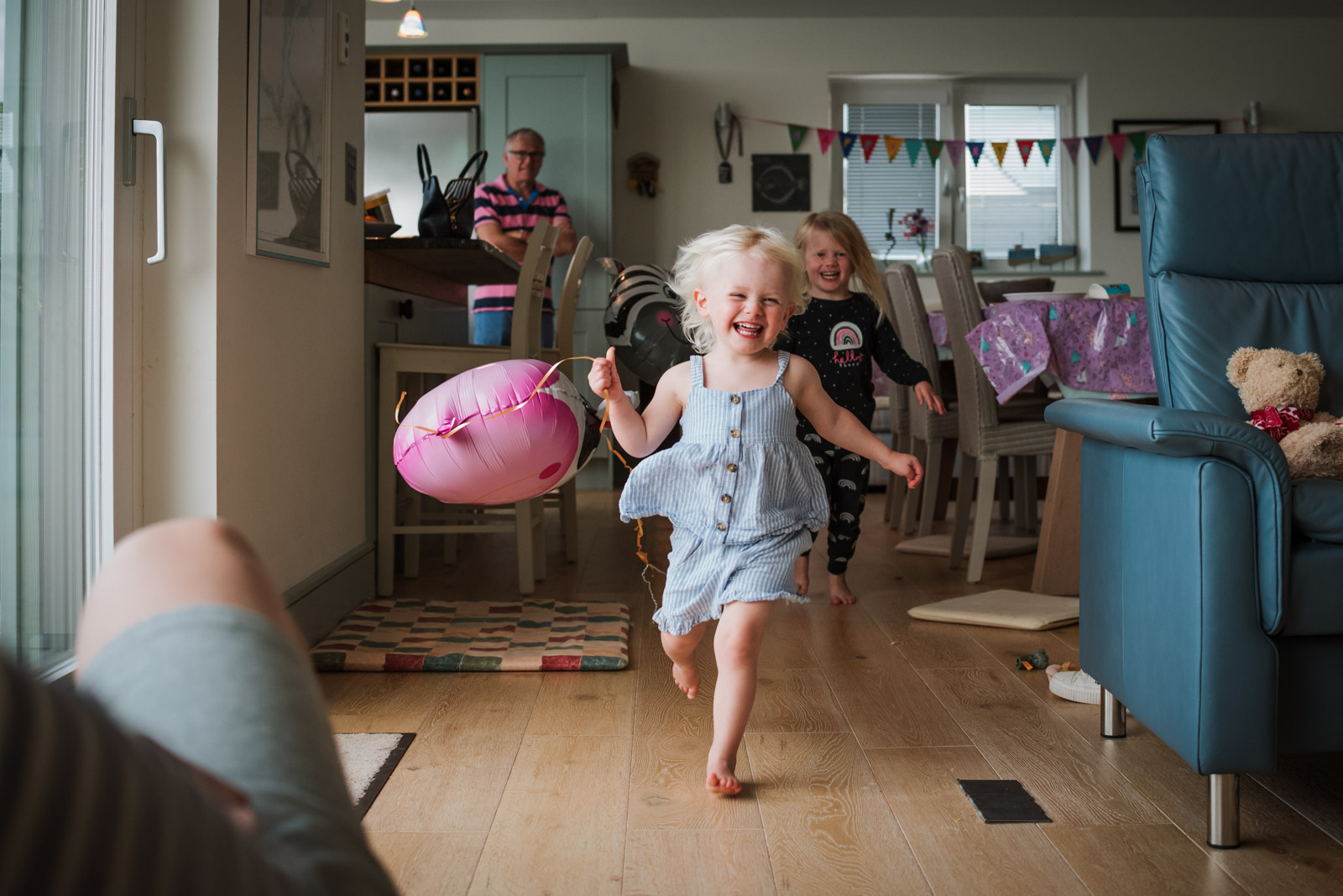 Best natural family photographer in Berkshire, girl running with a balloon