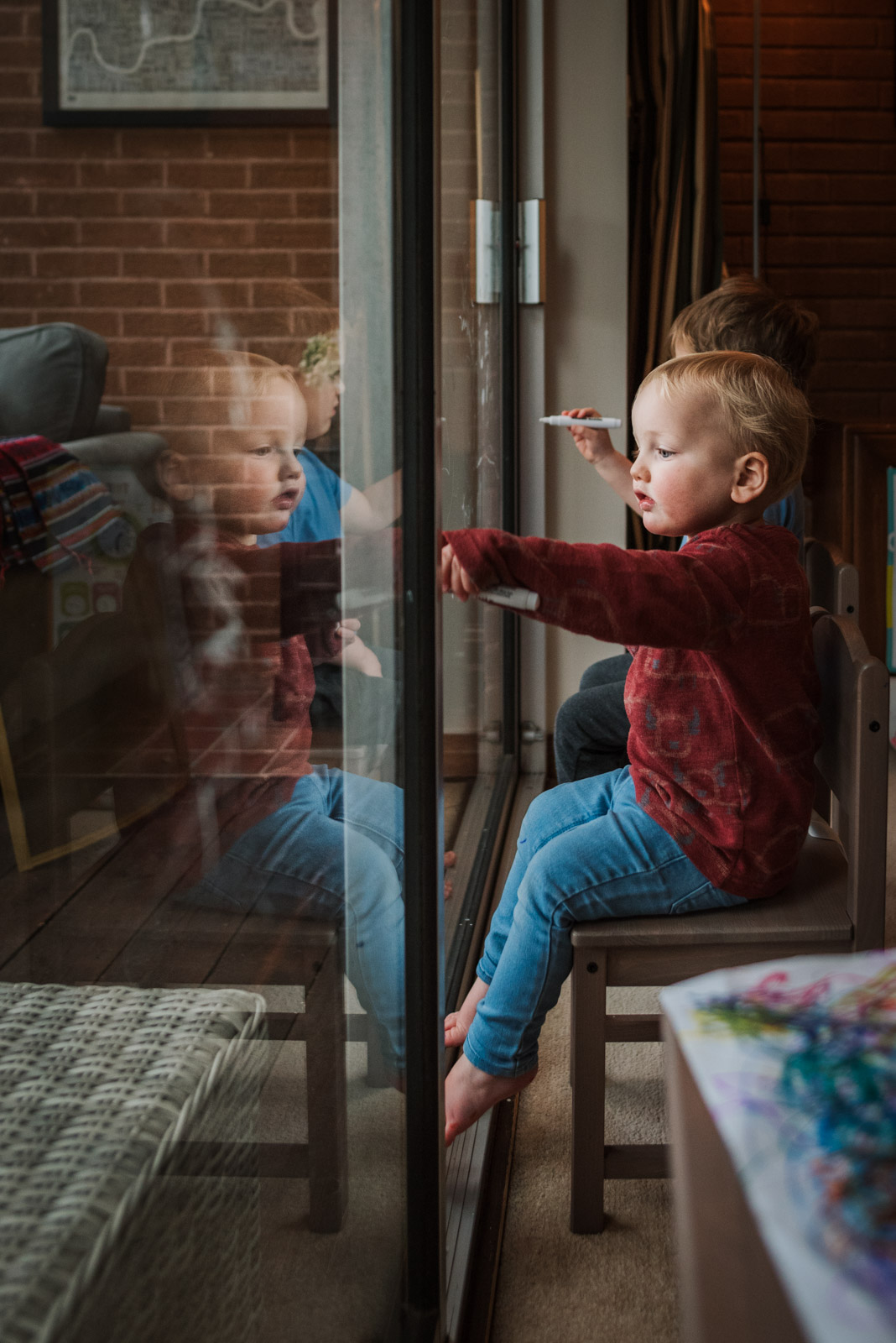 Emotive family photography, boy drawing on window, The Ginger Collective