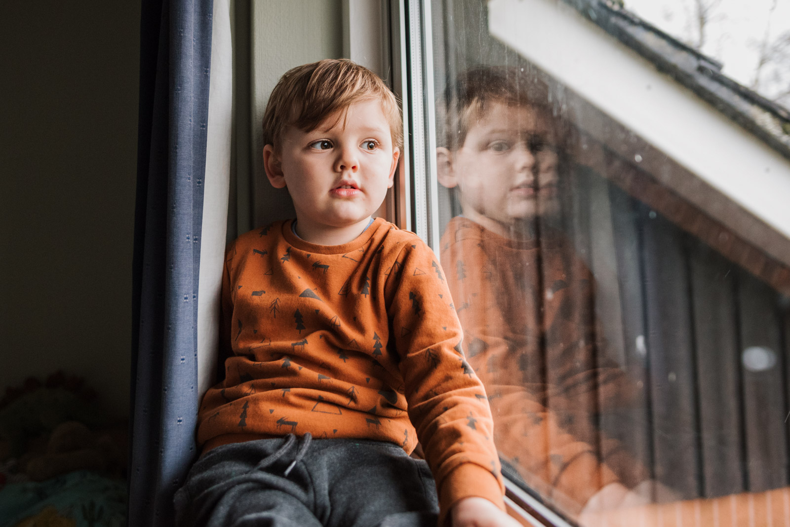 Natural family photography, boy looking out of window, The Ginger Collective