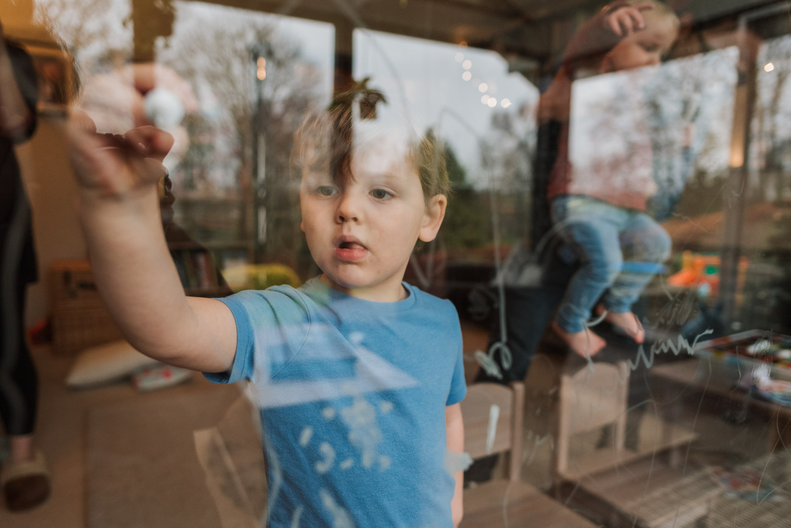 Unposed family photography, boy writing on glass, The Ginger Collective