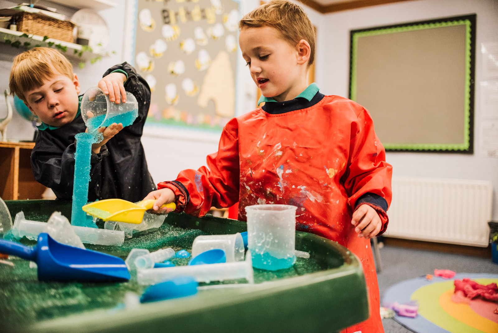 Relaxed brand photograph by The Ginger Collective of boys playing with slime at Berkshire school Thorngrove