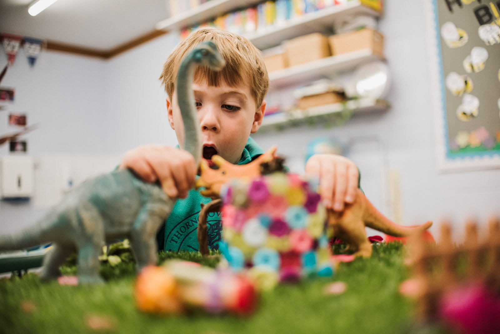 Natural and relaxed brand photograph by The Ginger Collective of boy playing with dinosaurs at Berkshire school Thorngrove